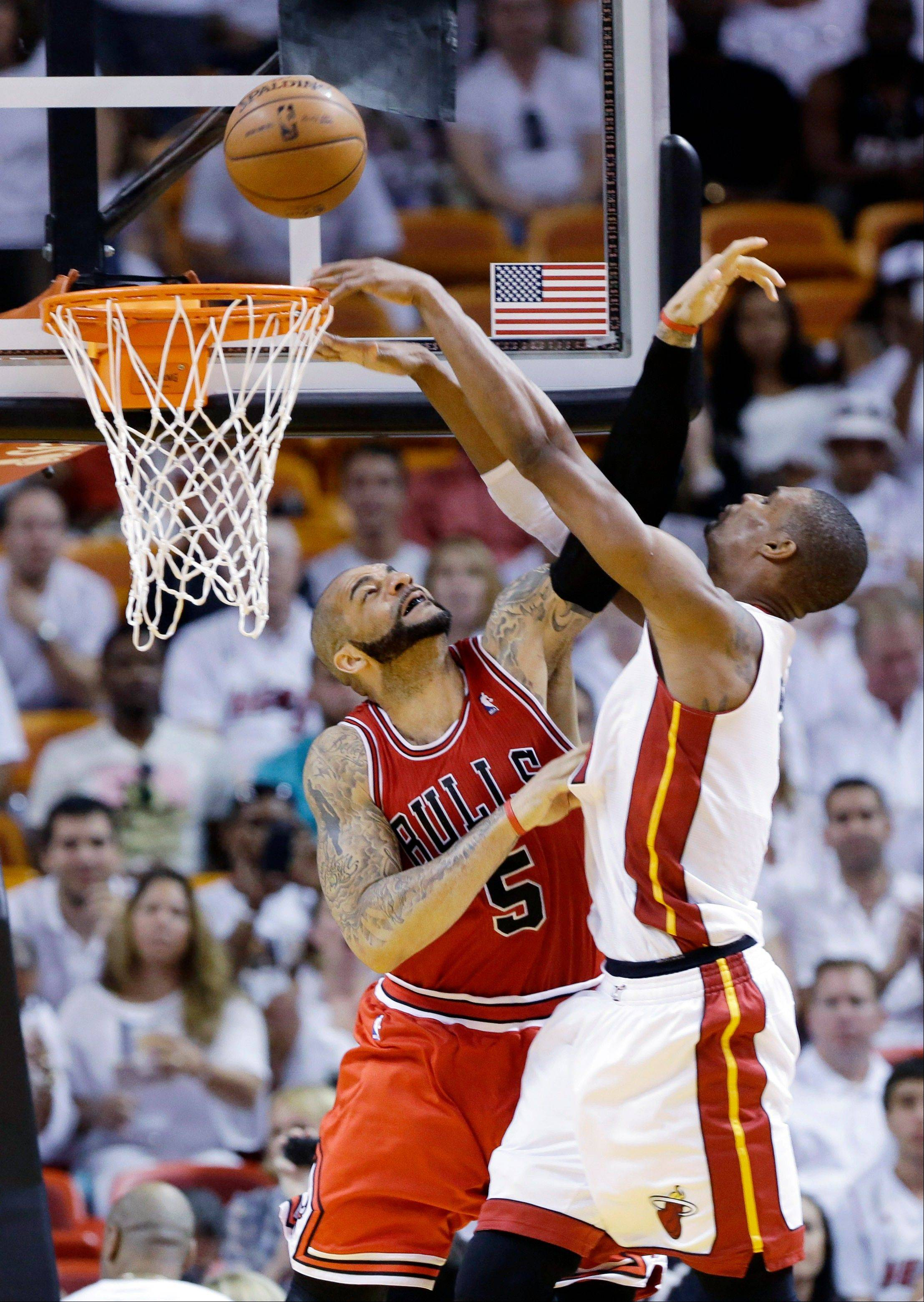 Miami Heat center Chris Bosh, right, is fouled by Chicago Bulls forward Carlos Boozer (5) as he goes up for a shot during the second half of Game 2 of their NBA basketball playoff series in the Eastern Conference semifinals, Wednesday, May 8, 2013, in Miami.