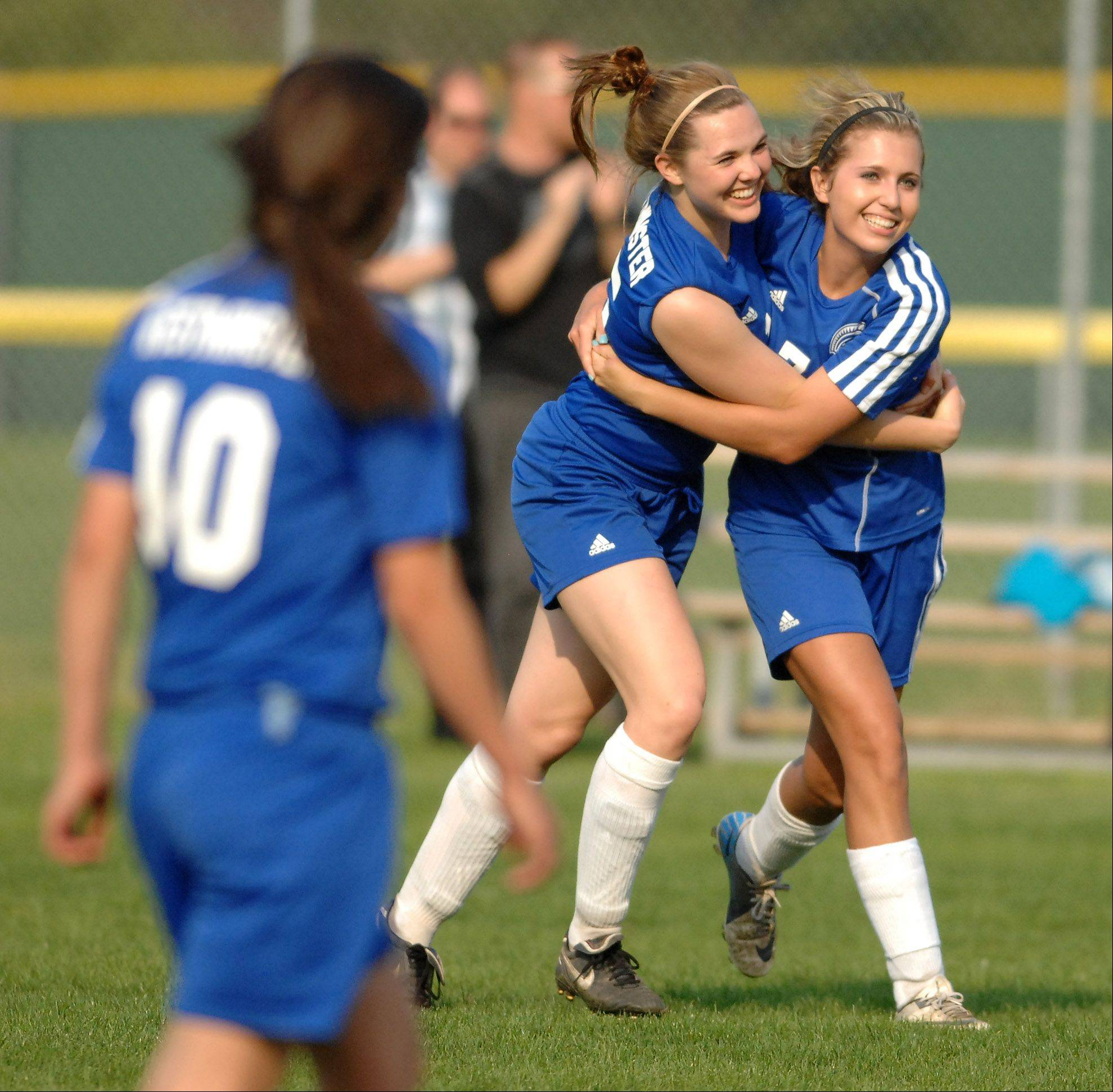 Westminster Christian's Helen Berntson, left center, hugs teammate Taylor Pedersen as the final whistle blows in their win over Harvest Christian during Wednesday's Class 1A regional semifinal in Elgin.