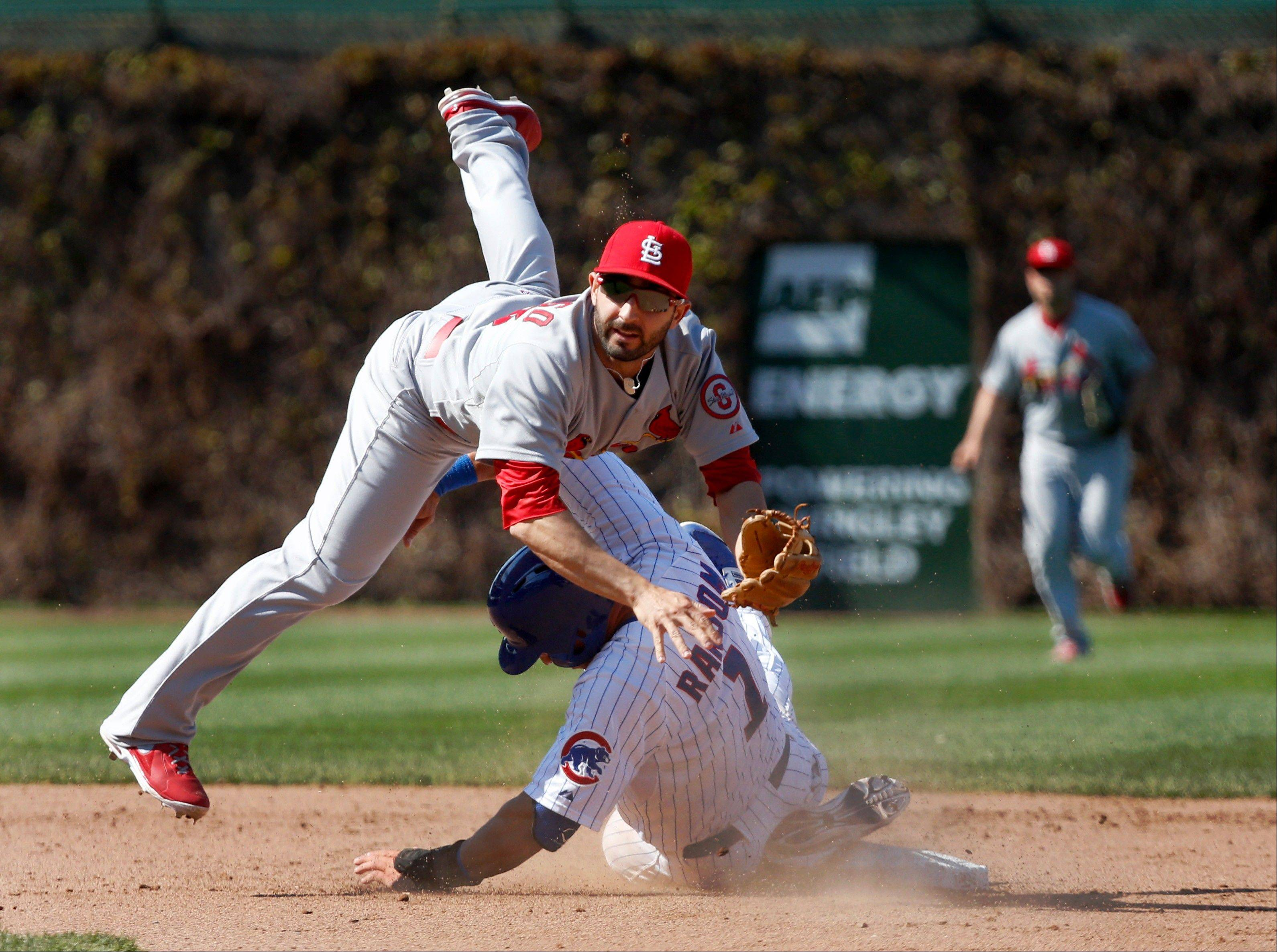 St. Louis Cardinals second baseman Daniel Descalso, top, turns the double play after forcing Chicago Cubs' Cody Ransom at second base during the seventh inning of a baseball game, Wednesday, May 8 2013, in Chicago. The Cubs' David DeJesus was out at first.