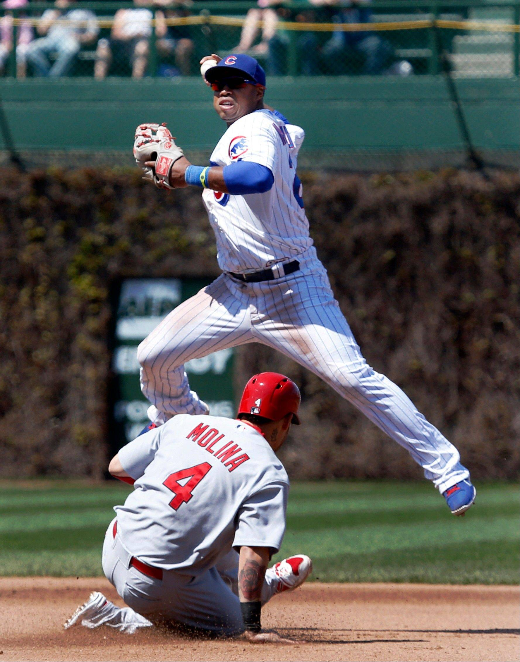 Cubs second baseman Luis Valbuena turns a double play after forcing out St. Louis Cardinals' Yadier Molina at second during the fourth inning of a baseball game Wednesday, May 8 2013, in Chicago. The Cardinals' David Freese was out at first.