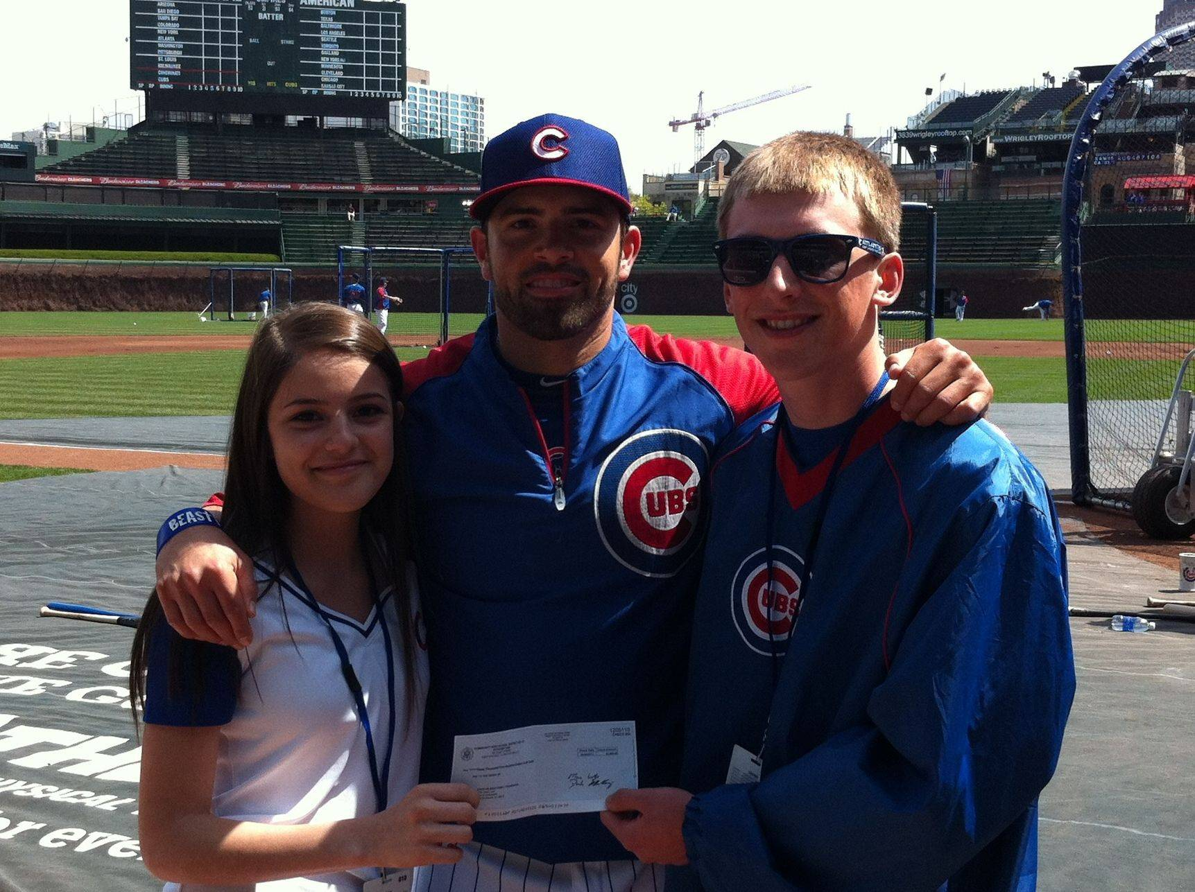Chicago Cubs outfielder David DeJesus poses with West Chicago students Luci Diaz, left, and Kyle Nielson, right, after they presented DeJesus with a $3,500 check for his charitable foundation.