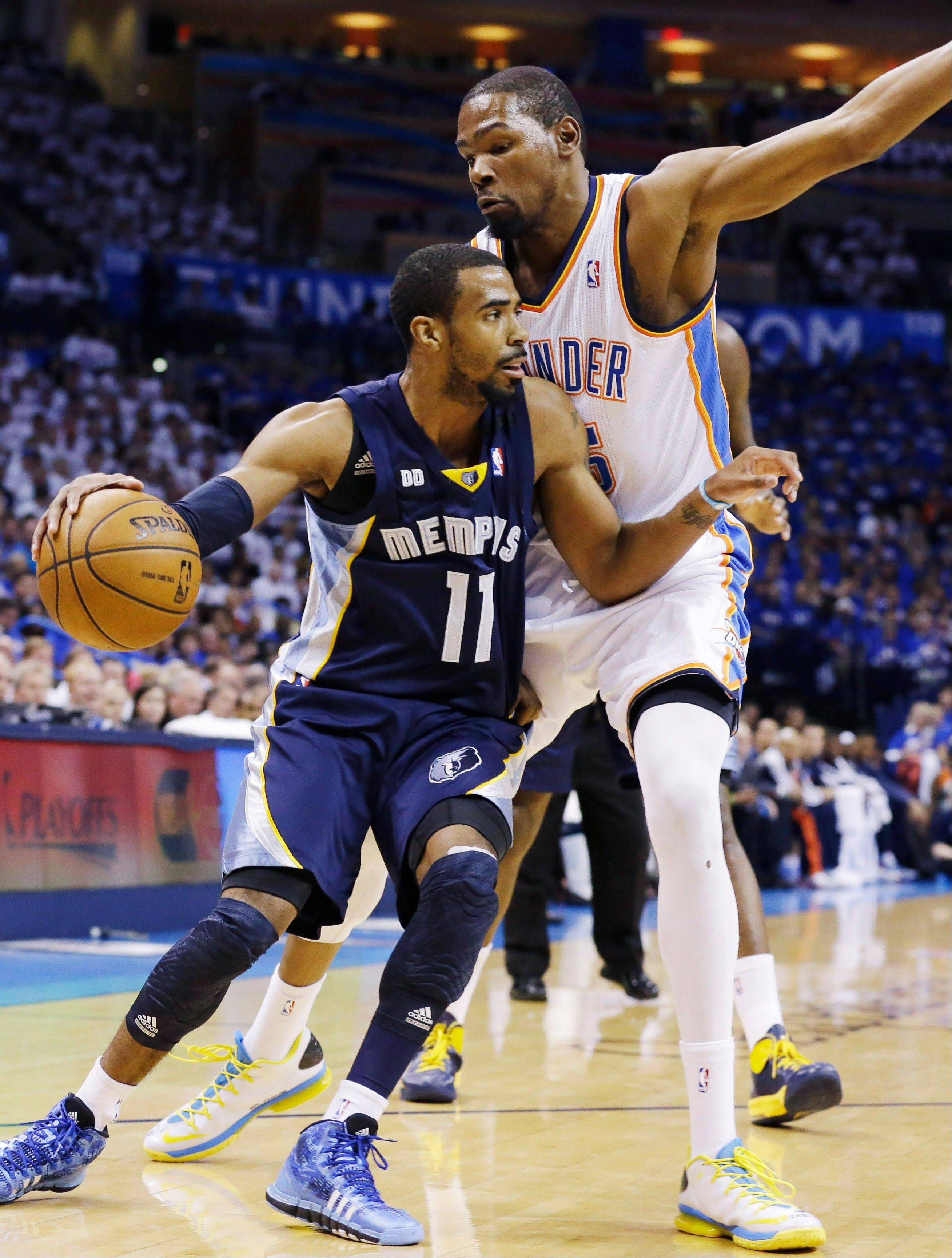 Memphis Grizzlies point guard Mike Conley (11) drives around Oklahoma City Thunder small forward Kevin Durant (35) during the first half at Game 2 of their Western Conference semifinal NBA basketball playoff series Tuesday, May 7, 2013, in Oklahoma City.