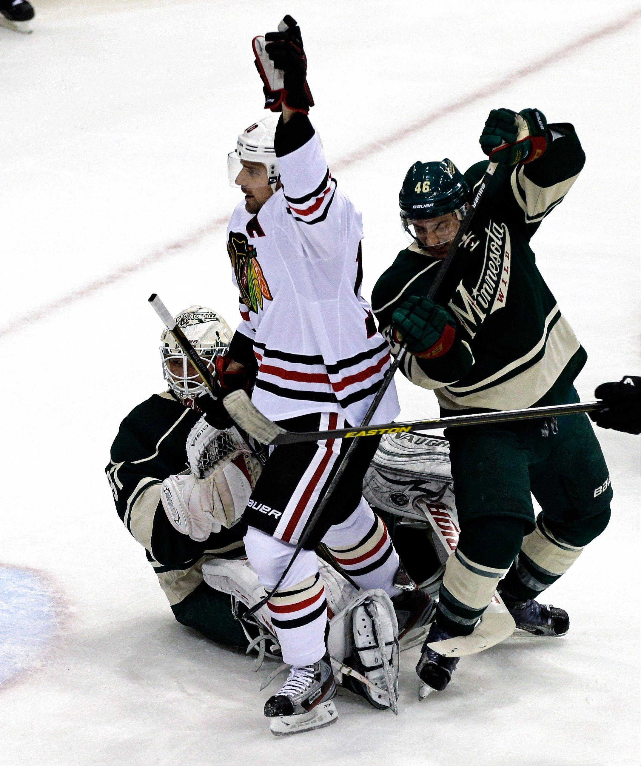 Chicago Blackhawks' Patrick Sharp, center, celebrates his goal off Minnesota Wild goalie Josh Harding, left, in the first period of Game 4 of an NHL hockey Stanley Cup playoff series, Tuesday, May 7, 2013 in St. Paul, Minn. At right is Wild's Jared Spurgeon.