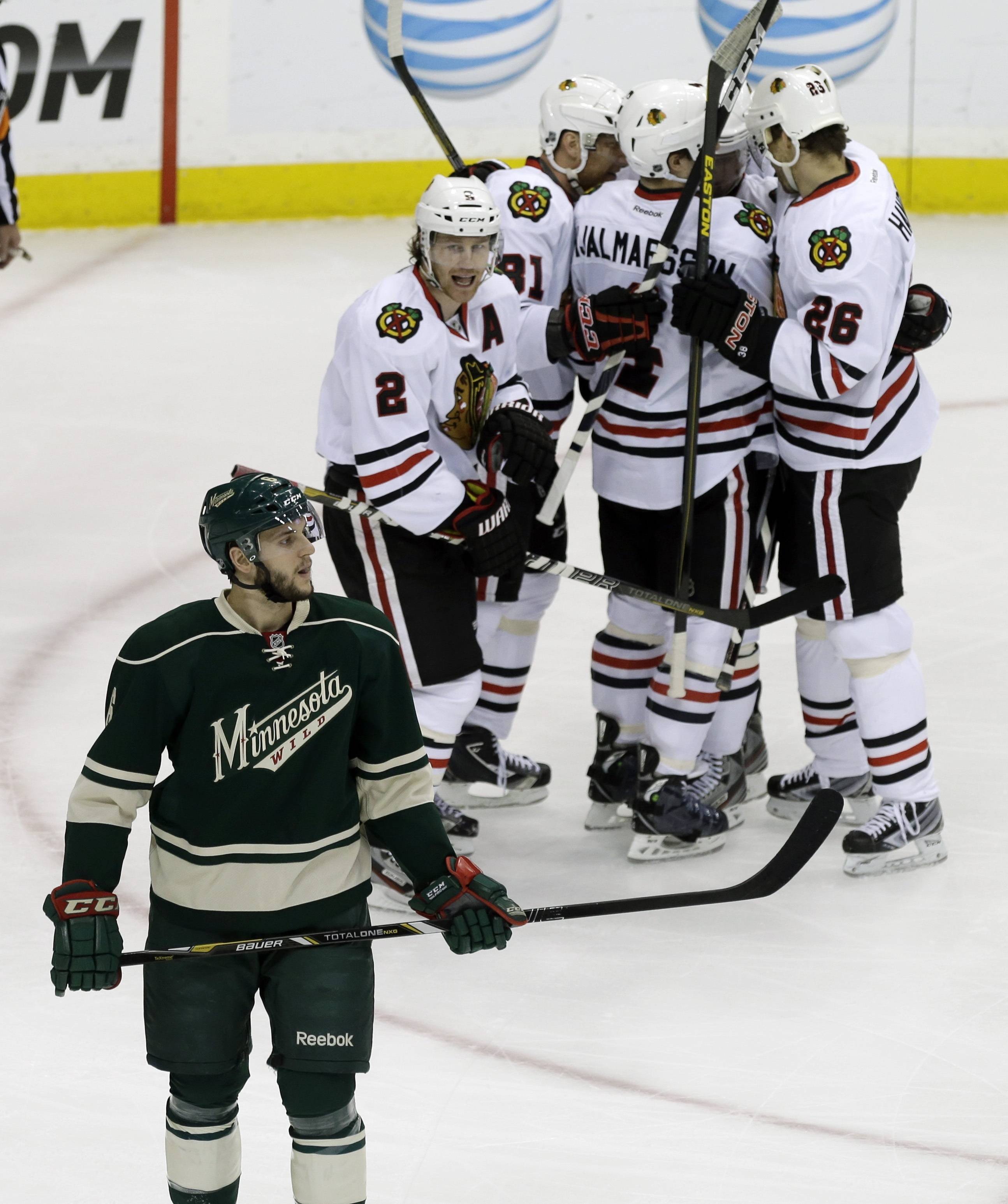 Chicago Blackhawks' Duncan Keith, top left, reacts toward Minnesota Wild's Marco Scandella, left, as Blackhawks players swarm around Patrick Sharp to celebrate his goal off Minnesota Wild goalie Josh Harding, bottom, in the first period of Game 4 of an NHL hockey Stanley Cup playoff series, Tuesday, May 7, 2013 in St. Paul, Minn. The Blackhawks won 3-0.