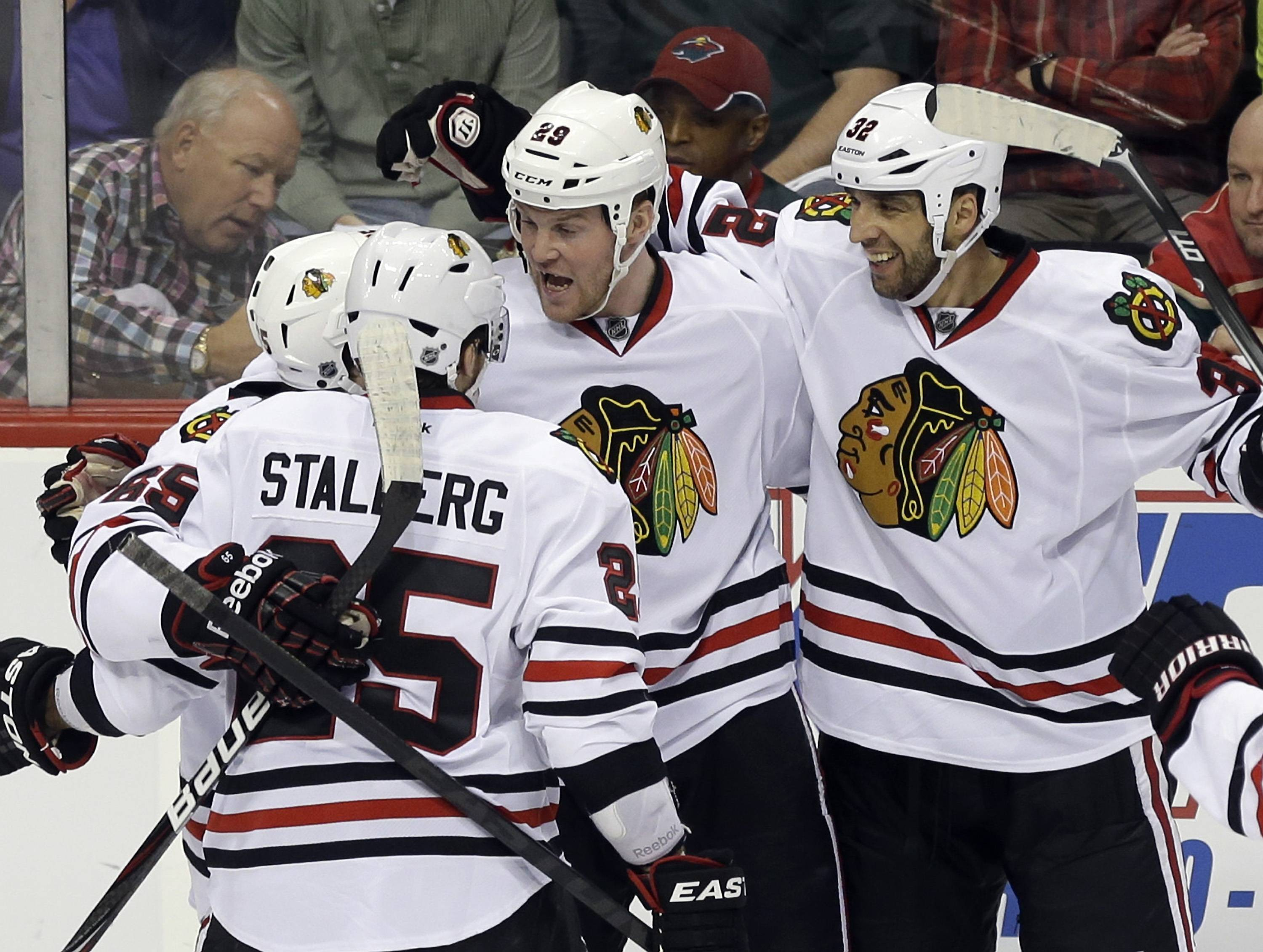 Chicago Blackhawks' Bryan Bickell, second from right, celebrates with teammates after he scored against Minnesota Wild backup goalie Darcy Kuemper in the third period of Game 4 of an NHL hockey Stanley Cup playoff series, Tuesday, May 7, 2013 in St. Paul, Minn. The Blackhawks won 3-0.
