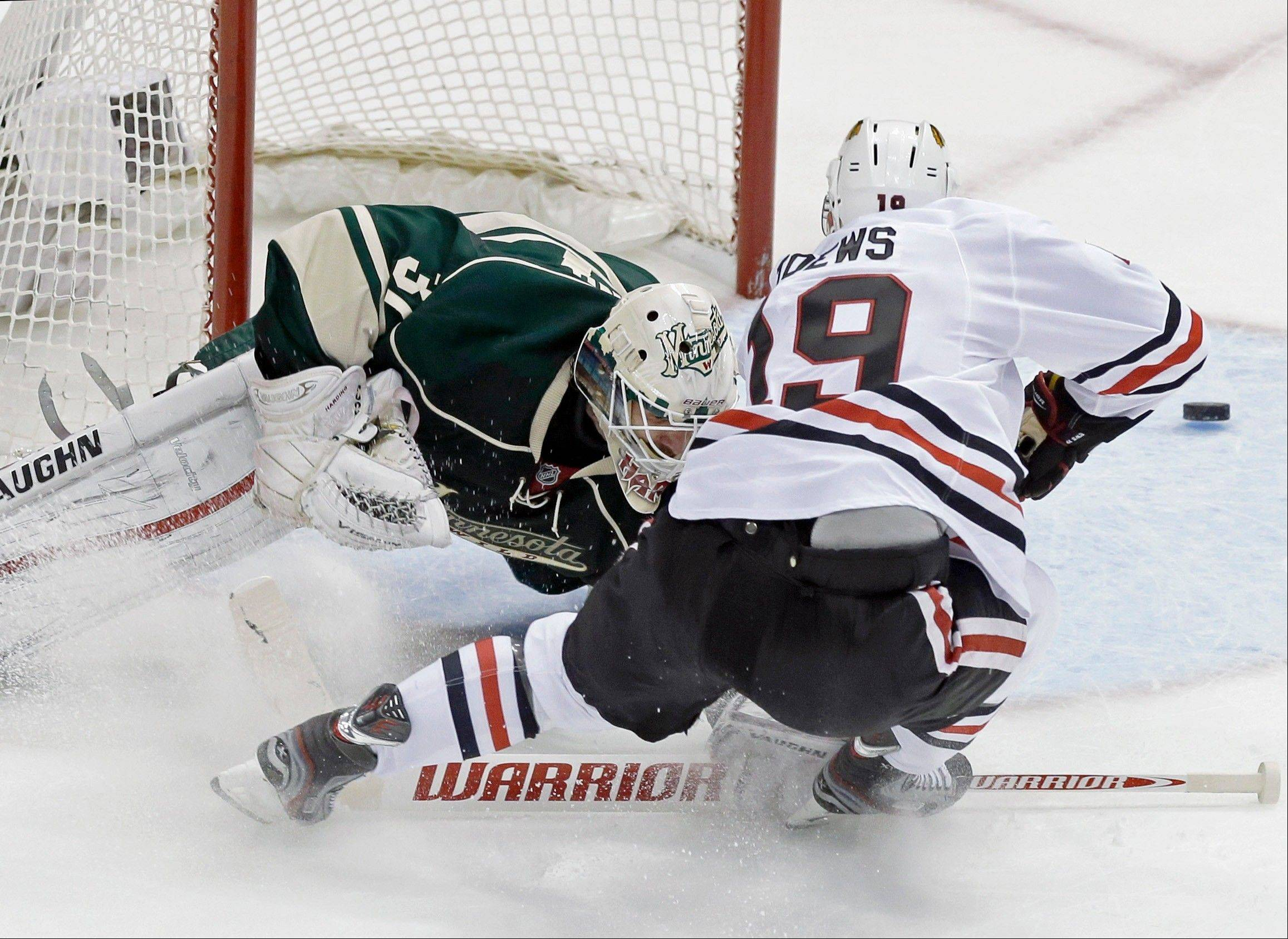 Minnesota Wild goalie Josh Harding, left, stops a shot by Chicago Blackhawks' Jonathan Toews in the first period of Game 4 of an NHL hockey Stanley Cup playoff series, Tuesday, May 7, 2013 in St. Paul, Minn. Harding was injured on the play and left the game after the first period.