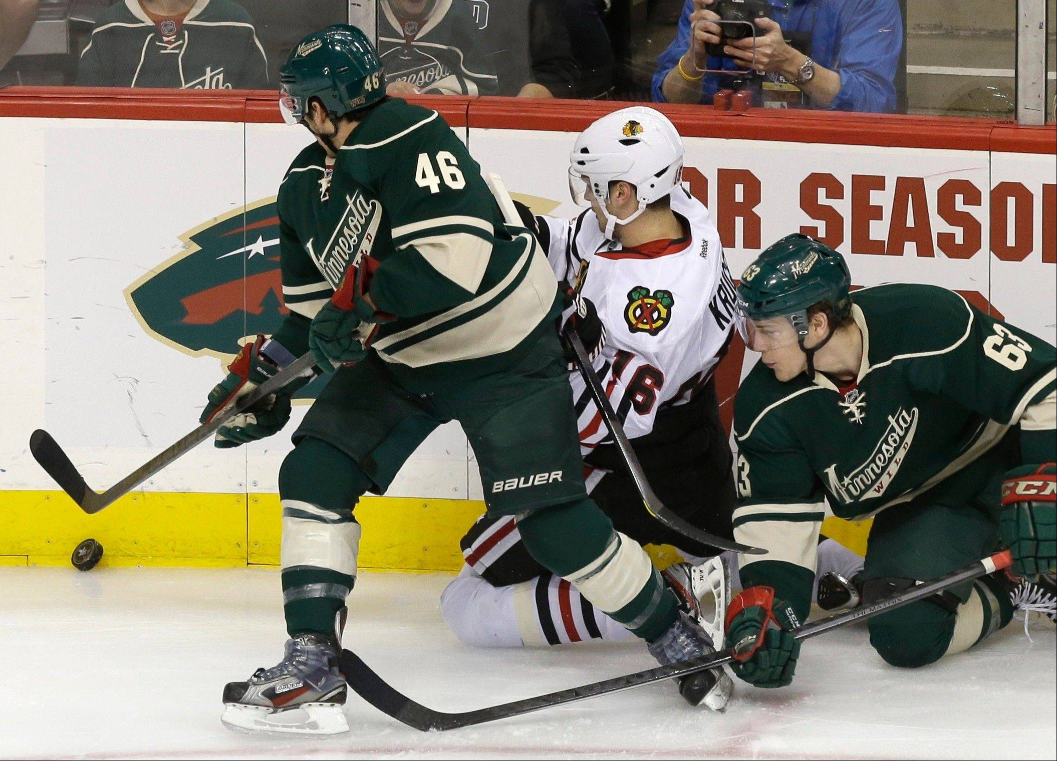 Chicago Blackhawks' Marcus Kruger, center, of Sweden gets squeezed out by Minnesota Wild's Jared Spurgeon, left, and Charlie Coyle in a race for the puck in the first period of Game 4 of an NHL hockey Stanley Cup playoff series, Tuesday, May 7, 2013 in St. Paul, Minn.