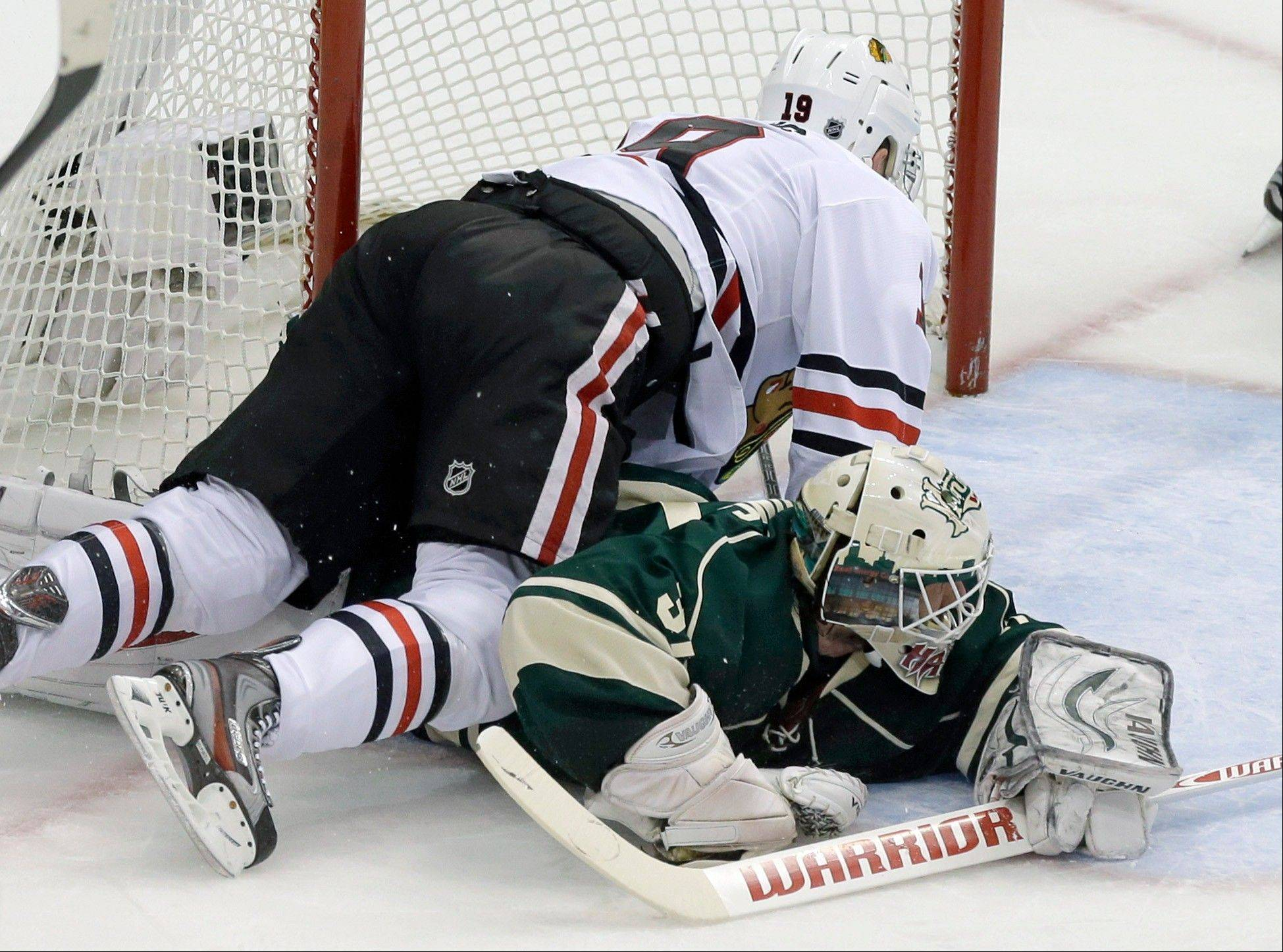 Chicago Blackhawks' Jonathan Toews, left, falls on Minnesota Wild goalie Josh Harding as Harding stoped a shot by Toews in the first period of Game 4 of an NHL hockey Stanley Cup playoff series, Tuesday, May 7, 2013 in St. Paul, Minn. Harding was injured on the play and left the game after the first period.