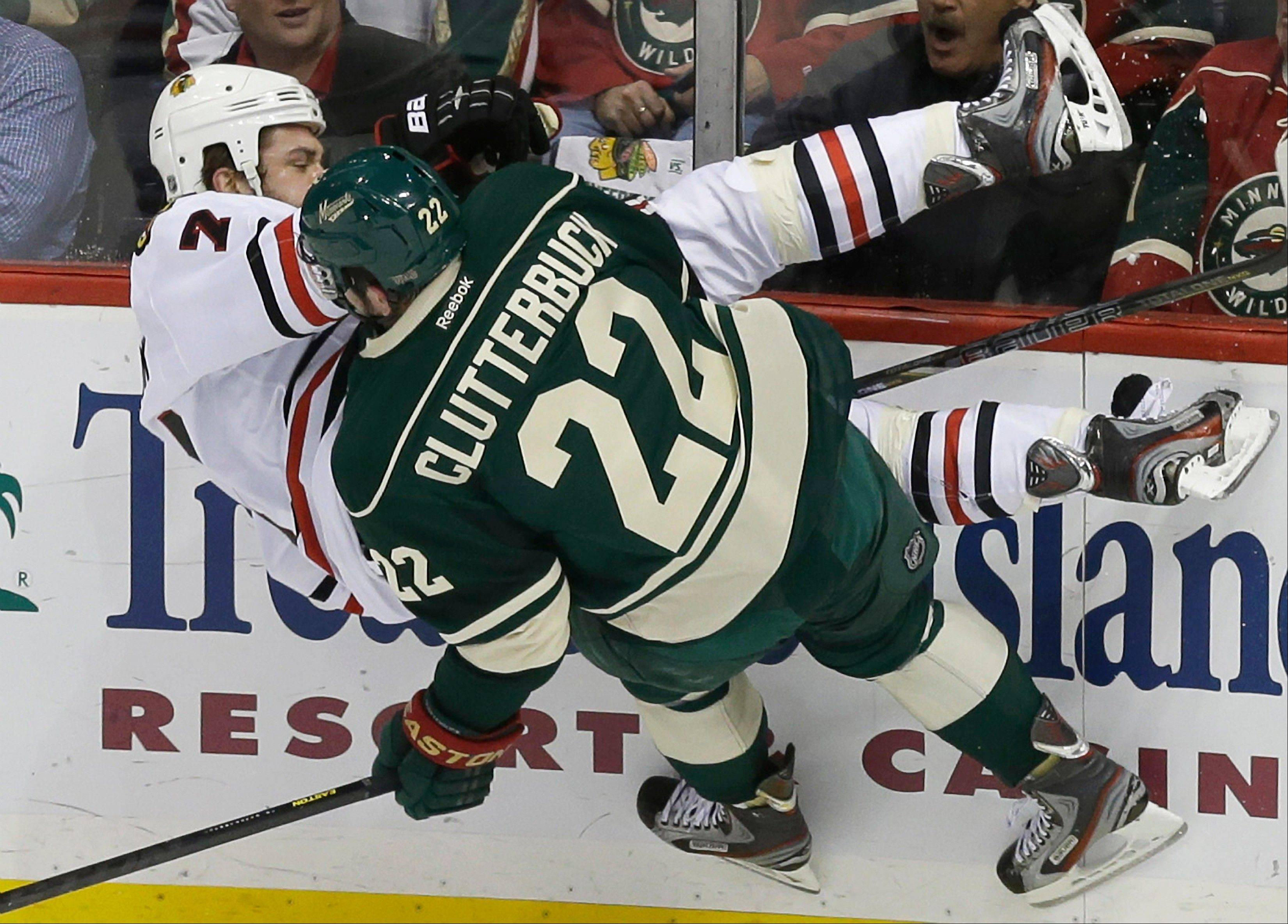 Chicago Blackhawks' Brent Seabrook gets checked into the wall by Minnesota Wild's Cal Clutterbuck in the first period of Game 4 of an NHL hockey Stanley Cup playoff series, Tuesday, May 7, 2013 in St. Paul, Minn.