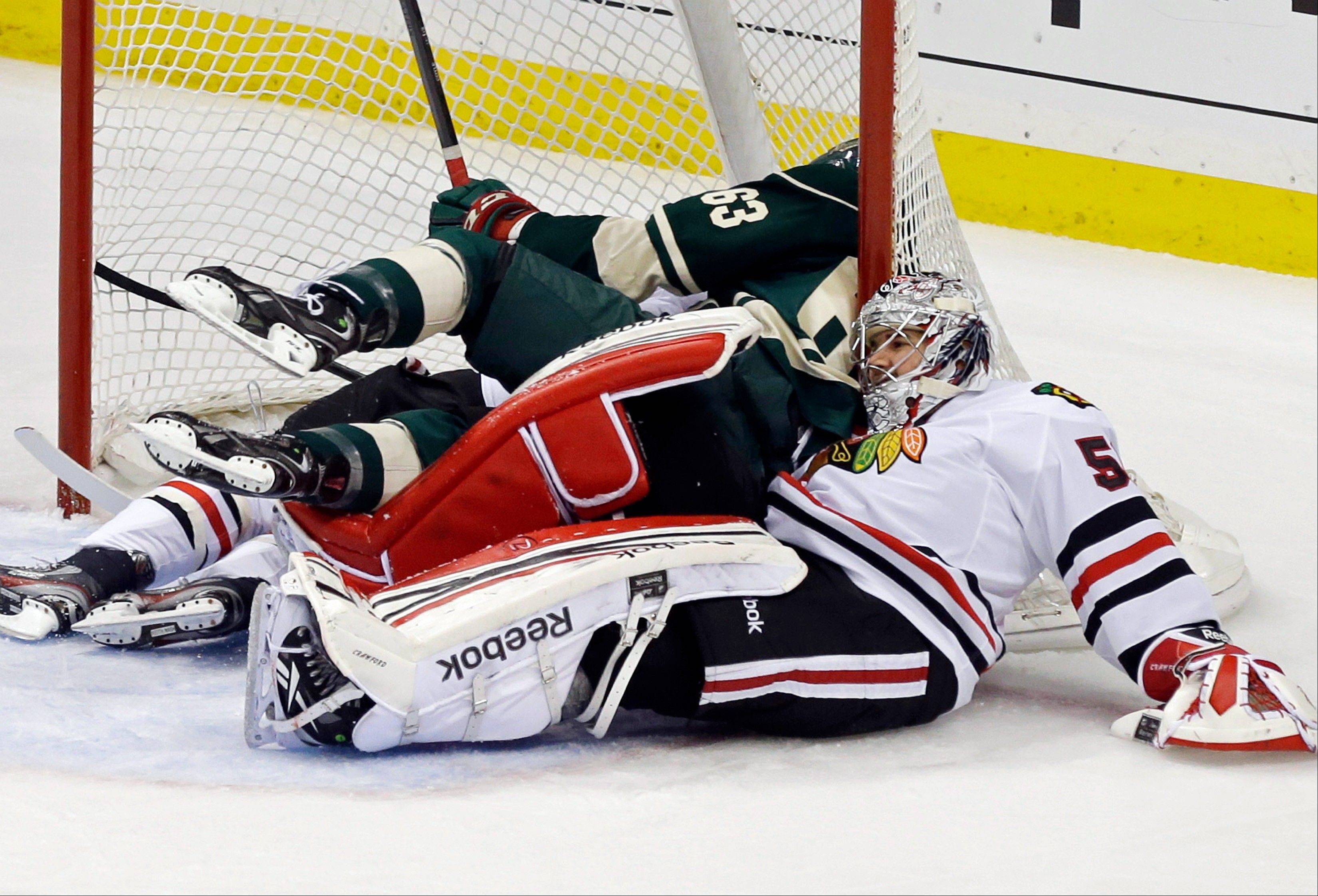 Chicago Blackhawks goalie Corey Crawford, right, winds up outside the goal as Blackhawks' Duncan Keith and Minnesota Wild's Charlie Coyle wound up in the goal in the first period of Game 4 of an NHL hockey Stanley Cup playoff series, Tuesday, May 7, 2013 in St. Paul, Minn.