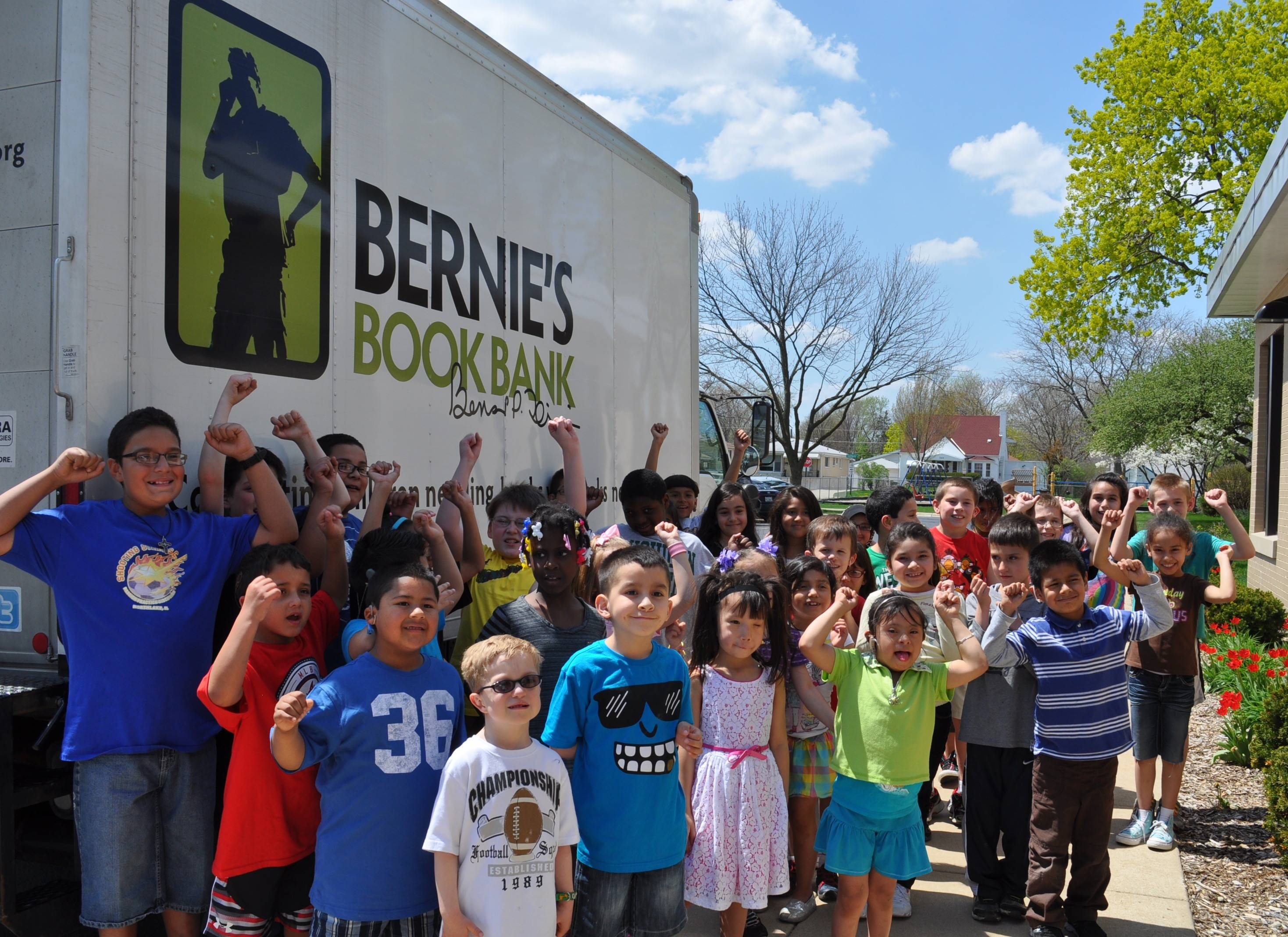 Students posing with Bernie's Book Bank truck after loading donated books.