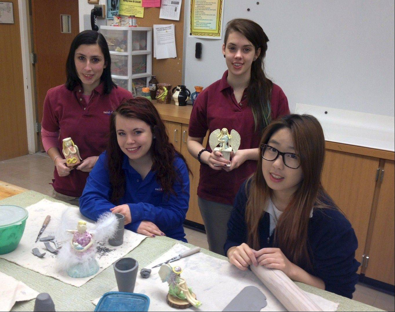 St Viator High School ceramics students share their angel figurines with the camera before sharing them with the world.