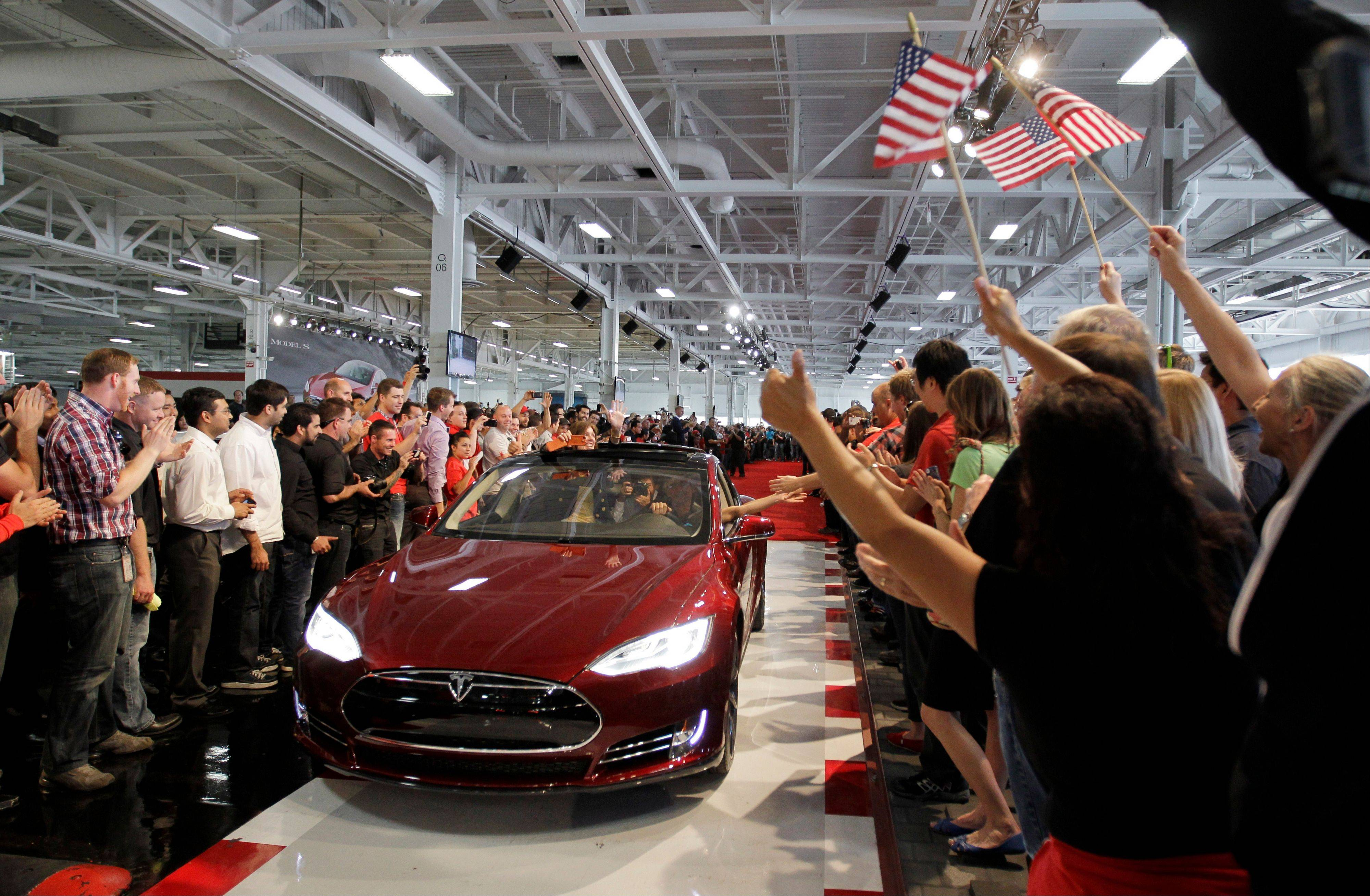 Tesla workers cheer on the first Tesla Model S cars sold during a rally at the Tesla factory in Fremont, Calif.