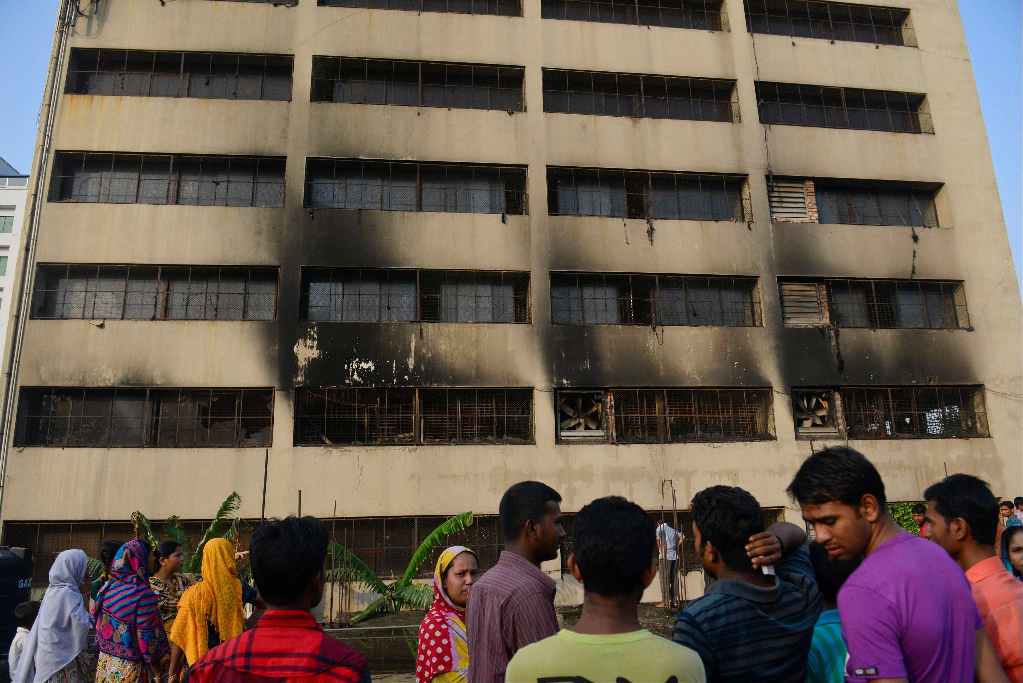Workers stand outside an 11-story building that houses the Tung Hai Sweater Ltd. factory and apartments after a fire in Dhaka, Bangladesh, Thursday, May 9, 2013. The fire broke out in the building Wednesday night, not long after the up to 300 workers of the factory went home for the day, killing at least eight people officials said Thursday.