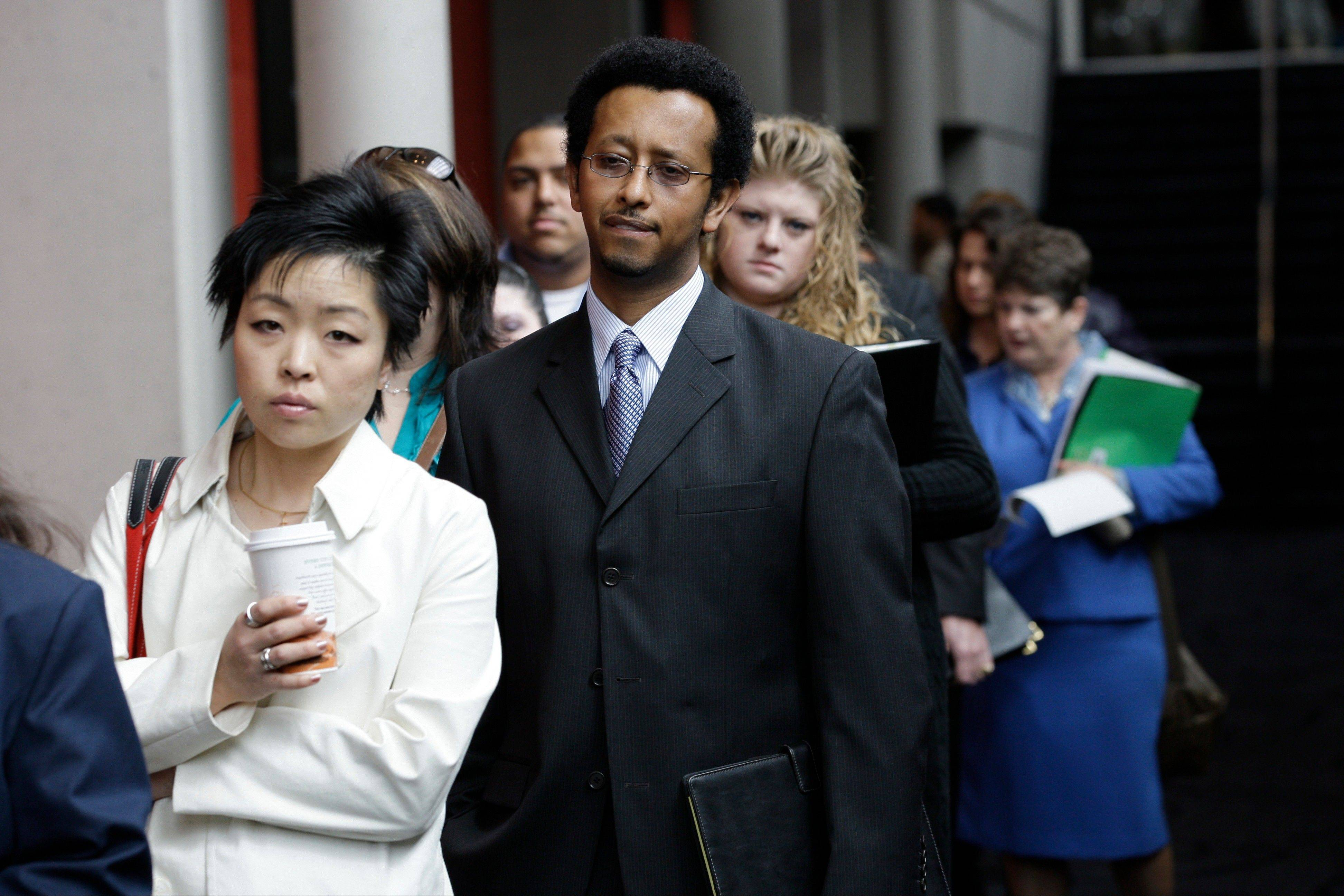 In this Tuesday, April 27, 2010, photo, Job-seekers, including Sophonias Gizaw, center, of Seattle, wait in line to attend a job fair, in Tacoma, Wash.