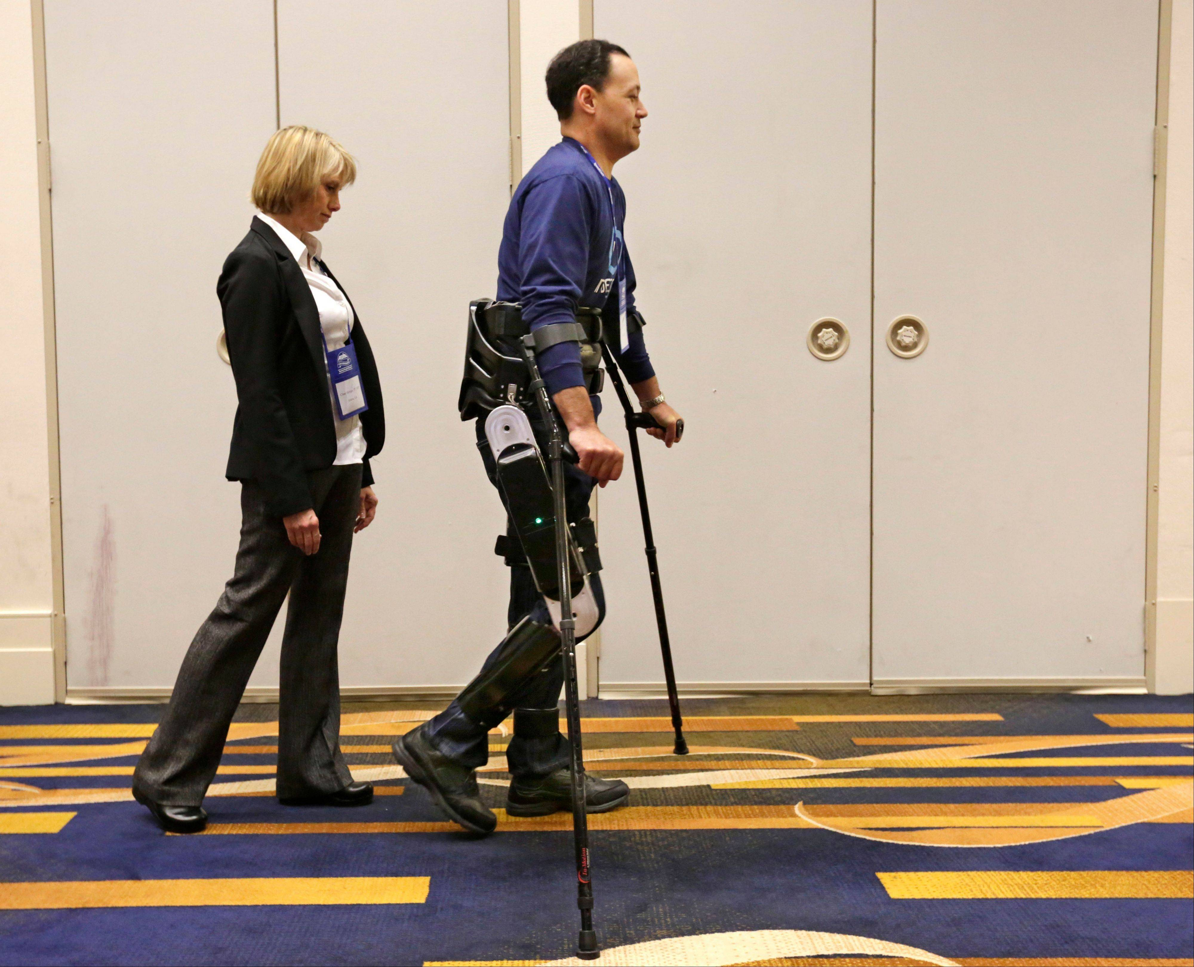 Michael Gore, who is paralyzed from a spinal injury, walks with the use of the Indego wearable robot under the supervision of physical therapist Clare Hartigan during a meeting of the American Spinal Injury Association at a downtown hotel in Chicago.