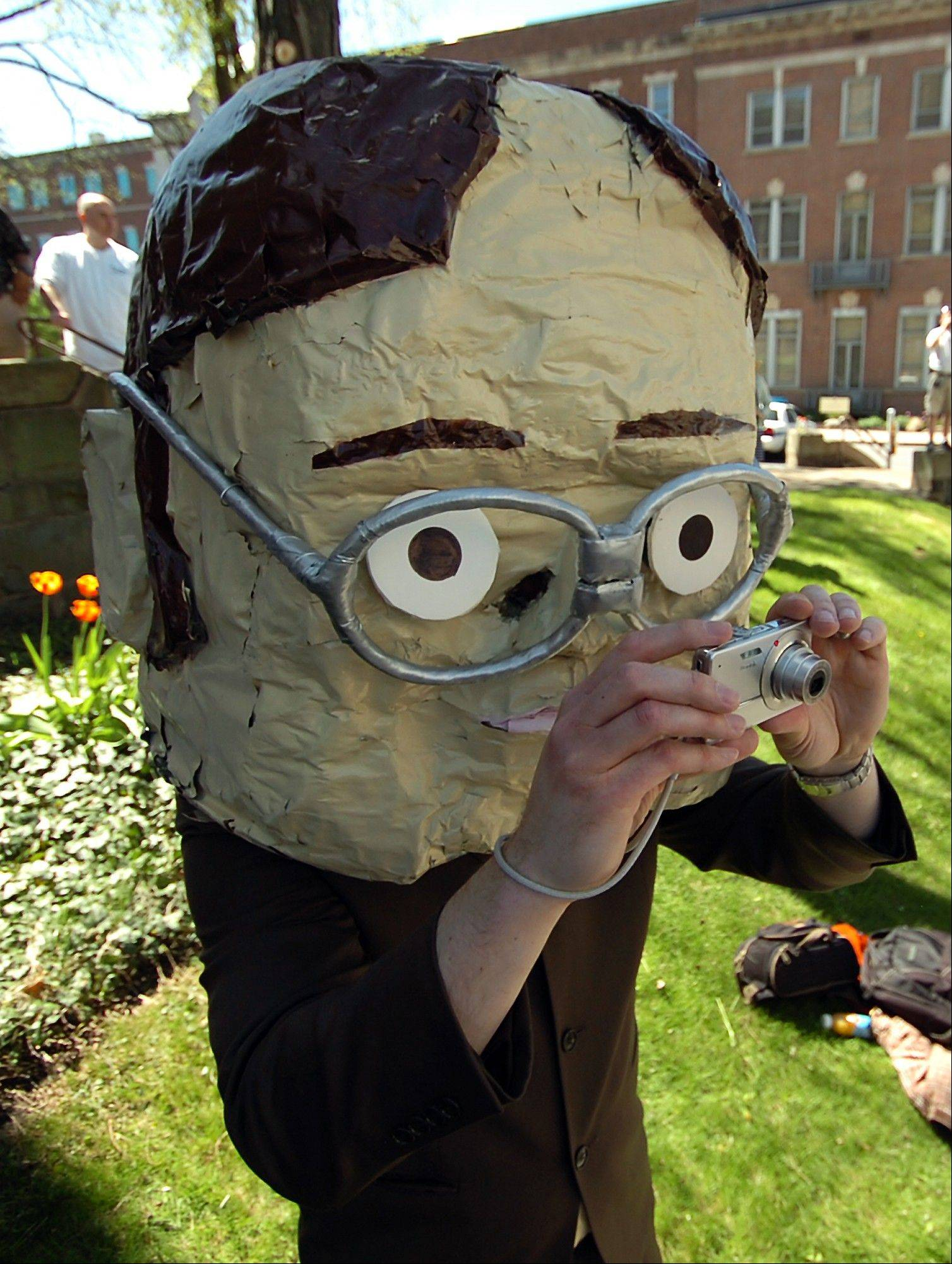"Chris Sedlak of Dayton, Ohio, wears a large bobble head mask depicting ""The Office"" character Dwight Schrute portrayed by actor Rainn Wison."