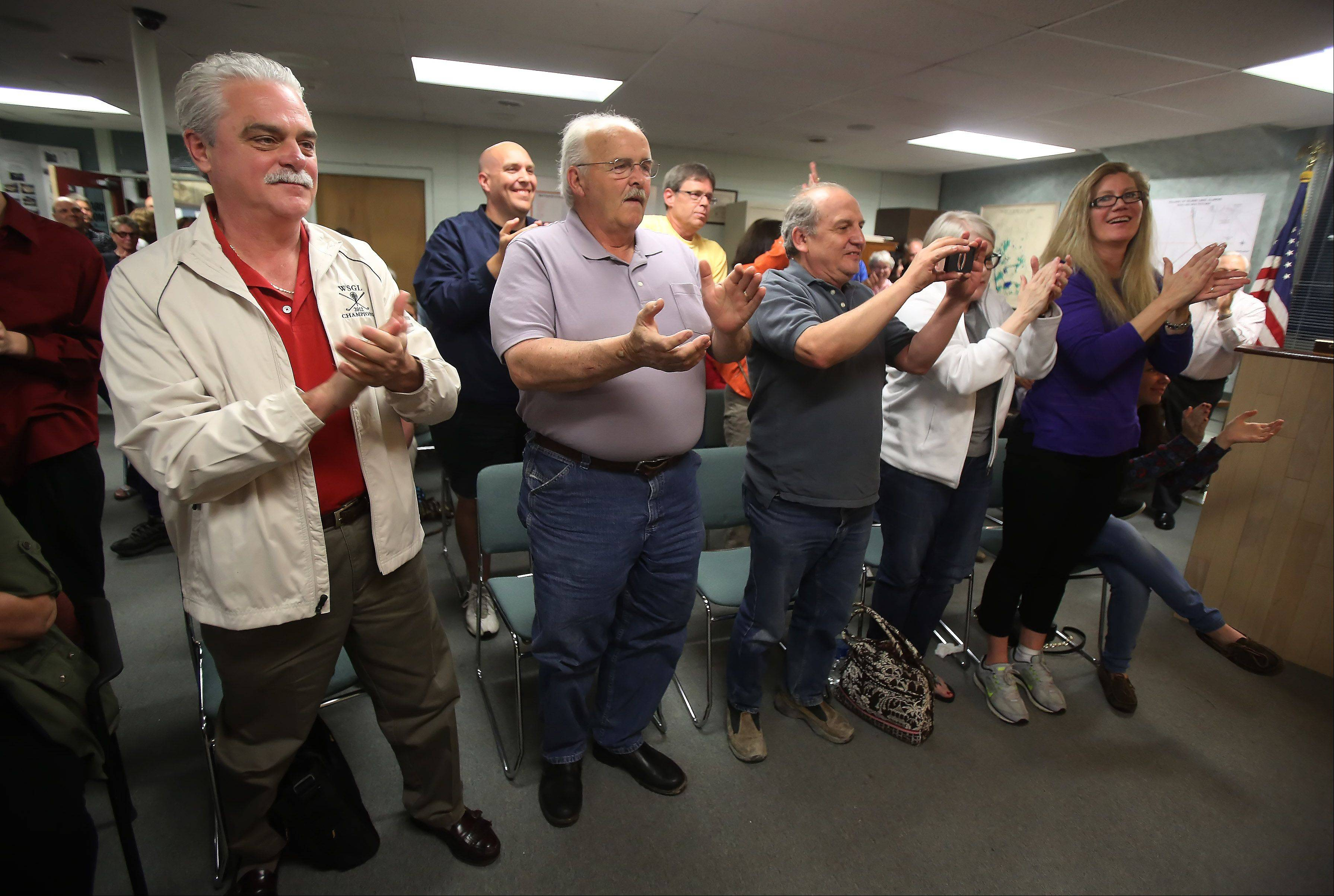 Gilbert R. Boucher II/gboucher@dailyherald.comA packed house breaks into applause Thursday after Charles Amrich is sworn in as the new Island Lake mayor at the village hall.