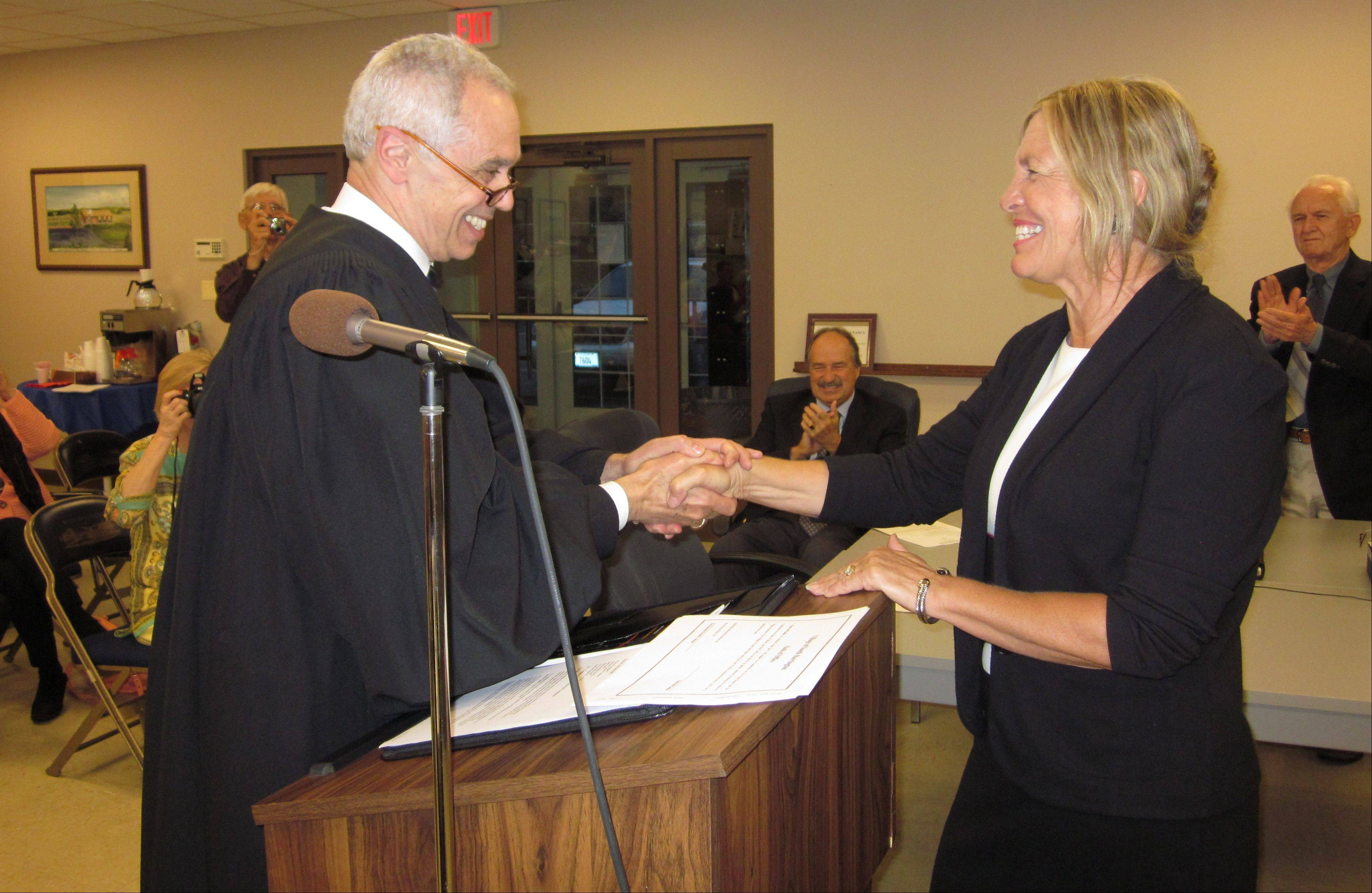 South Barrington Village Attorney Don Storino, who also serves as a judge with the Illinois Court of Claims, congratulates new South Barrington Village President Paula McCombie after she took her oath of office Thursday.
