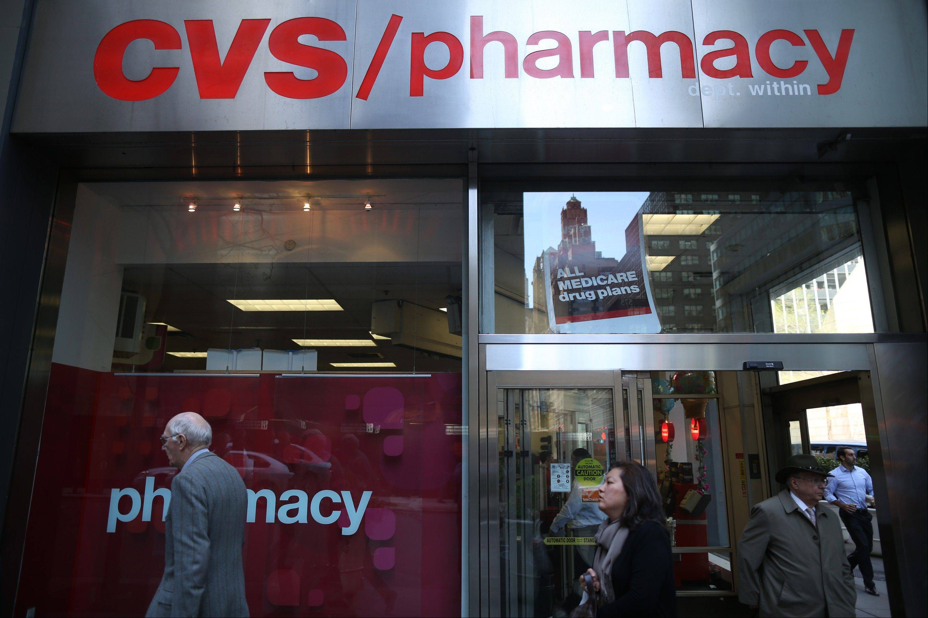 Pedestrians walk past a CVS Caremark Corp. store in New York.