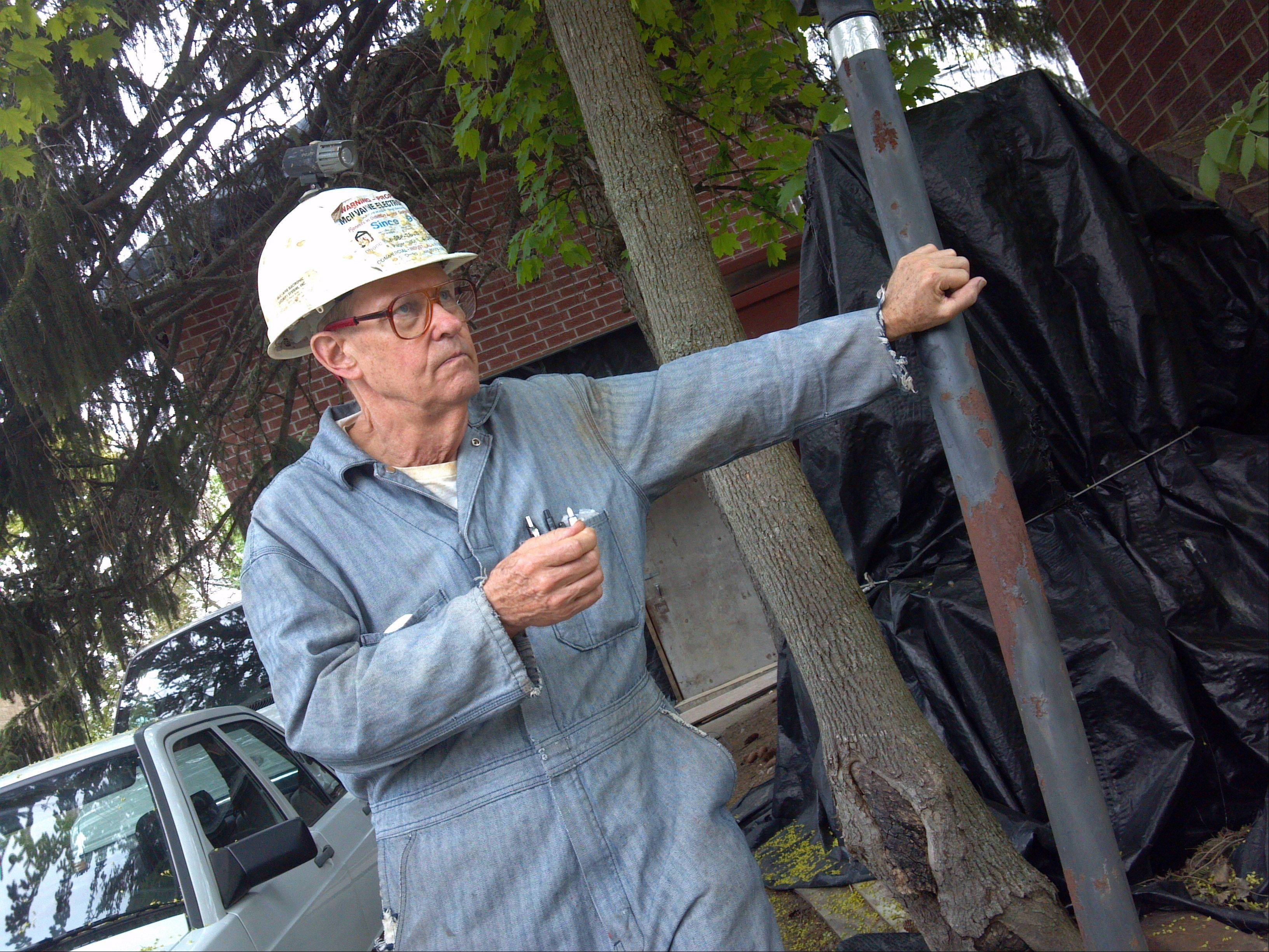 Clifford McIlvaine, a St. Charles homeowner under fire for a long-running construction project, talks Thursday outside his home on the 600 block of Prairie Street. A judge last week gave the city permission to make repairs and send McIlvaine the bill.