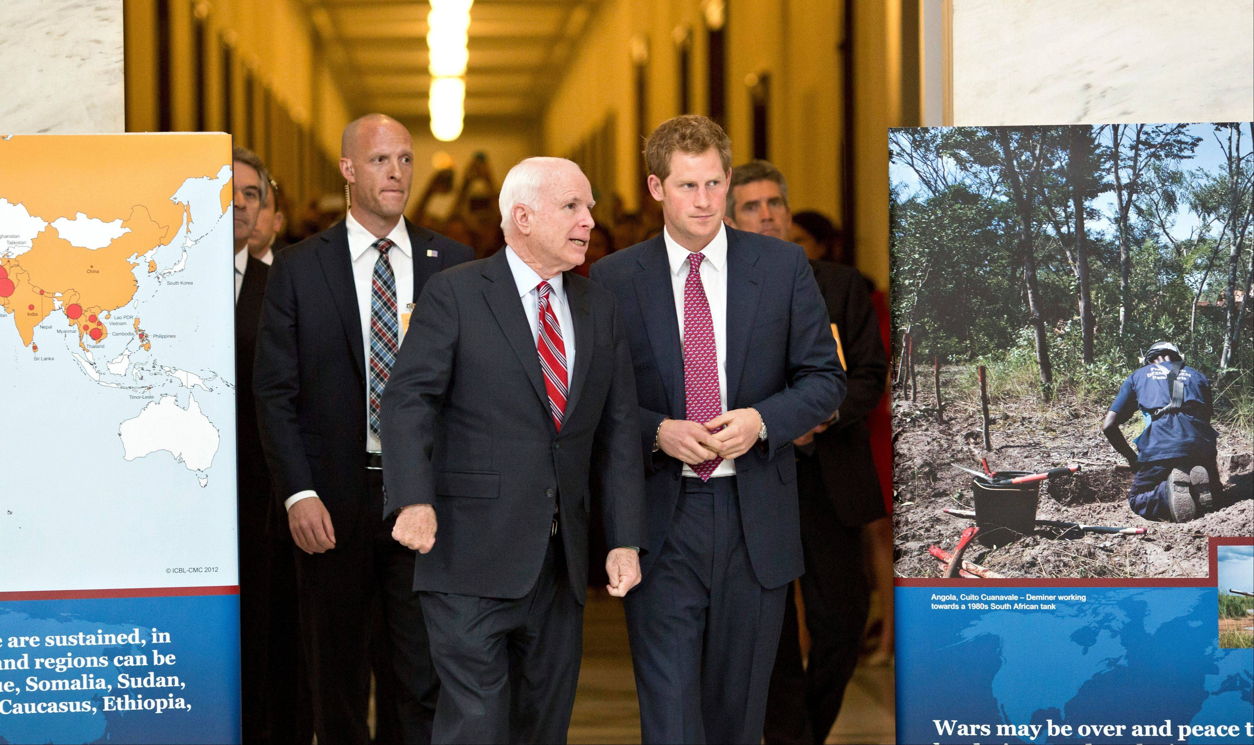 Britain's Prince Harry, center right, tours an exhibition on Capitol Hill Thursday in Washington staged by the HALO Trust, escorted by Sen. John McCain, R-Ariz..