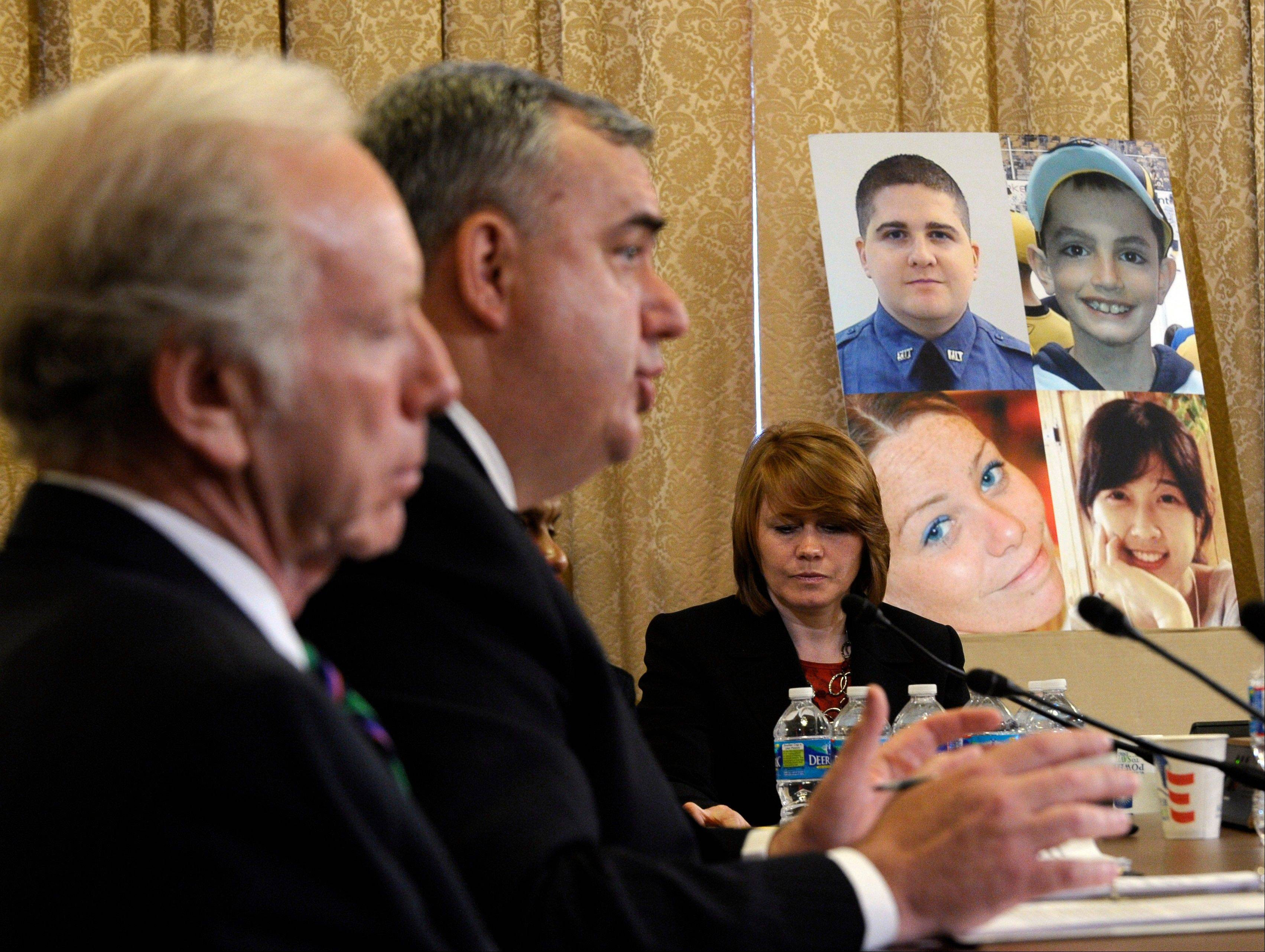 "Boston Police Commissioner Edward Davis testifies before the House Homeland Security Committee at a hearing on ""The Boston Bombings: A First Look,"" on Capitol Hill in Washington, Thursday, May 9, 2013. Former Sen. Joseph Lieberman, I-Conn., sits at left, and photos of those who were killed at the Boston Marathon bombing are at right."