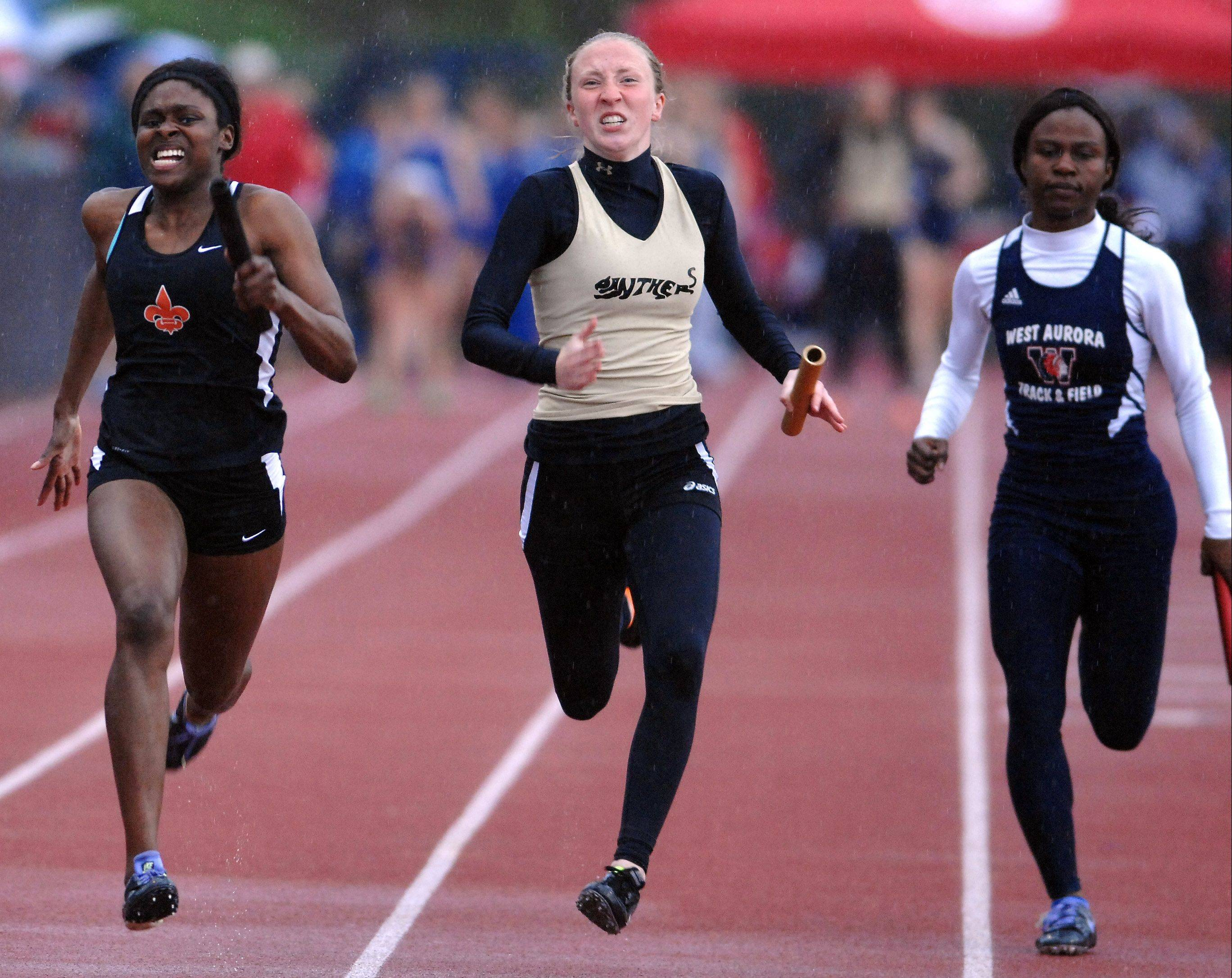 Brittney Williams of St. Charles East, left, Glenbard North's Sara Stankoskey and Snita Saffa of West Aurora anchor their teams to first-, second- and third-place finishes, respectively, in the 400-meter relay during the Class 3A West Aurora girls track and field sectional Thursday.