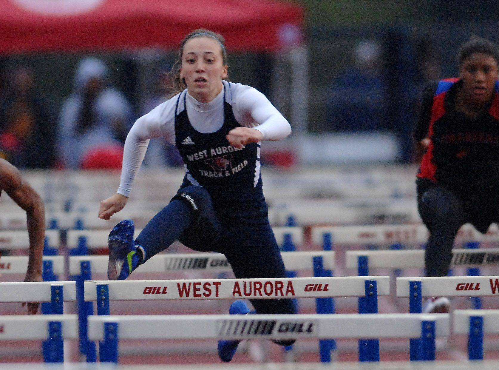 Emma Spagnola of West Aurora runs the 100-meter hurdles during the West Aurora girl's track sectional Thursday.