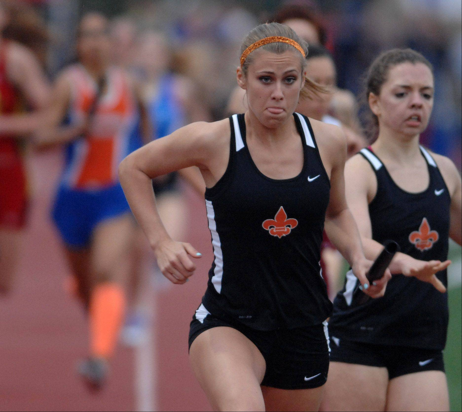 Krista Fitzmaurice of St. Charles East takes the baton to run her leg of the 3,200-meter relay during the Class 3A West Aurora girls track and field sectional Thursday.
