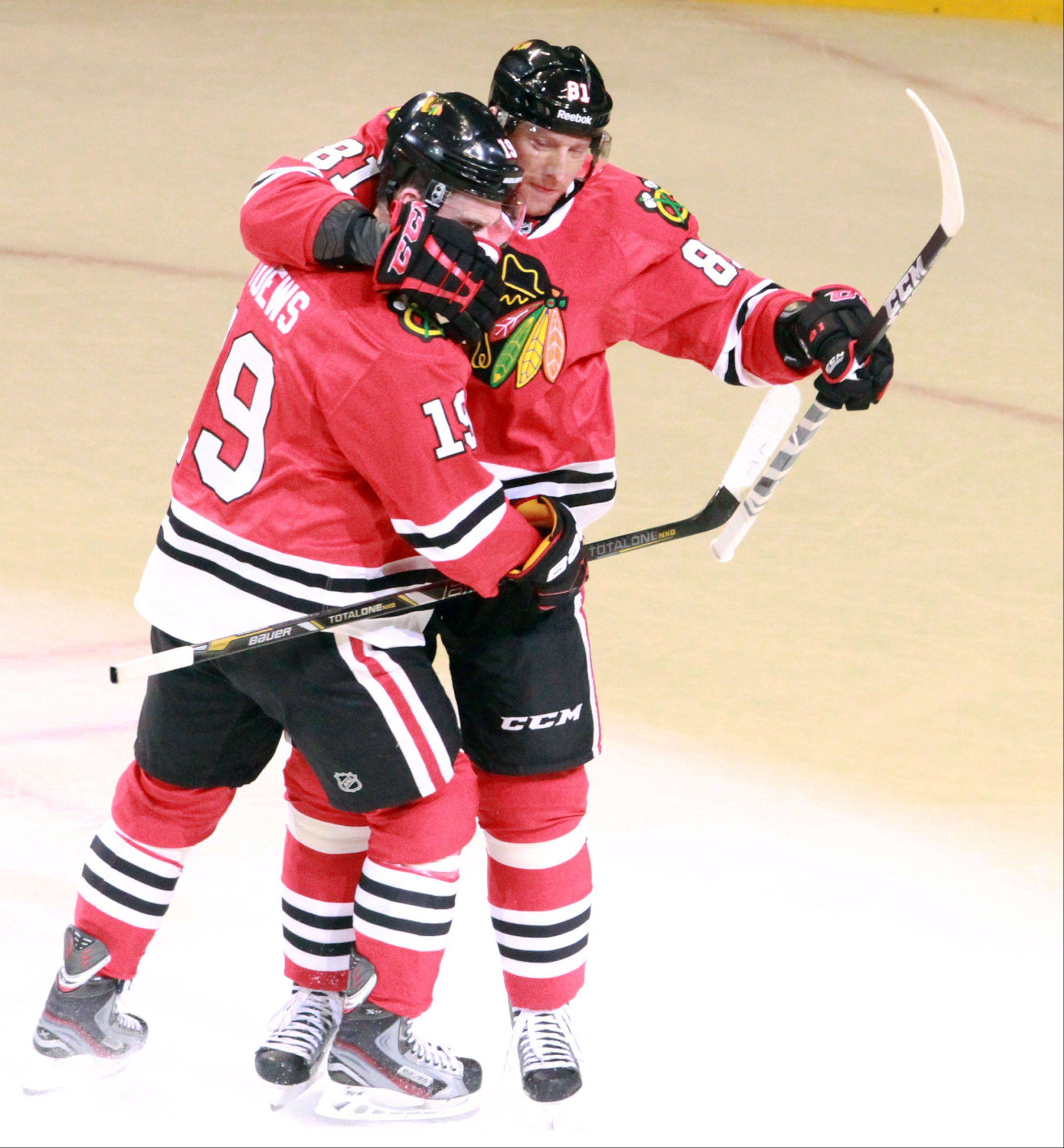 Blackhawks center Jonathan Toews celebrates a goal by right wing Marian Hossa against Minnesota Wild in game 5 of the NHL Western Conference first-round playoff series at the United Center Thursday.