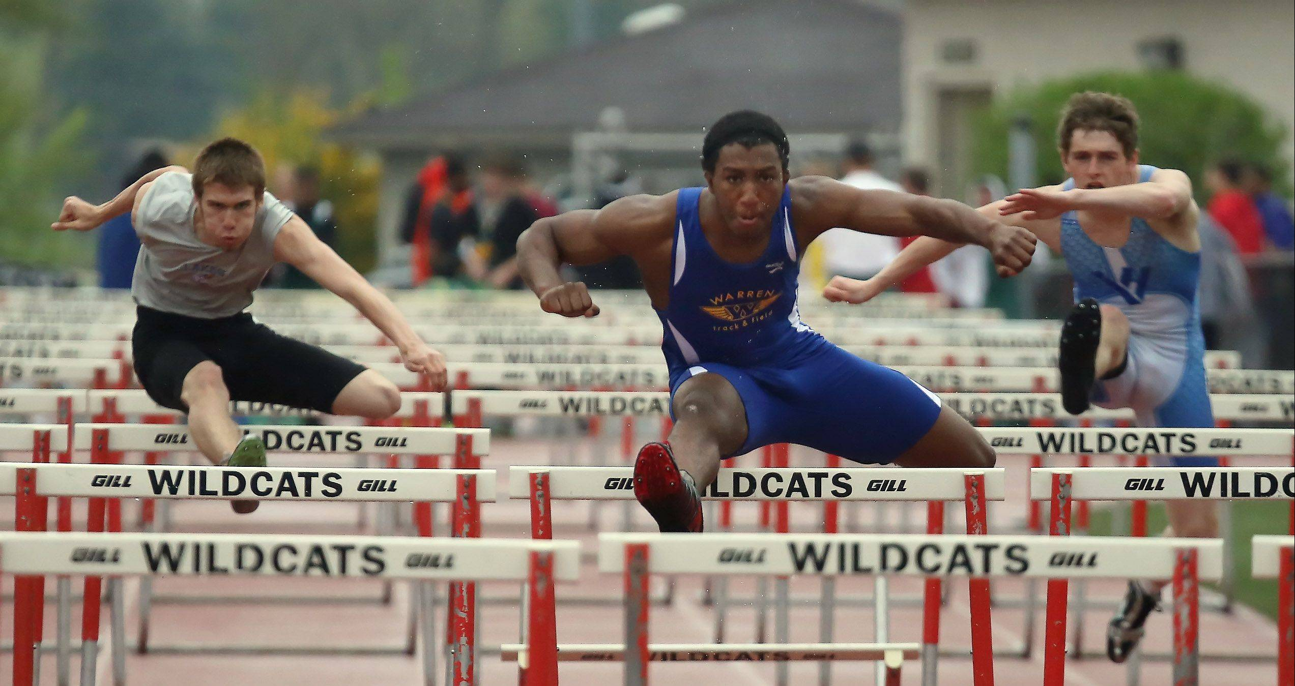 Warren's Myles Garner, center, wins his preliminary heat of the 110-meter hurdles during the North Suburban Conference boys track meet Thursday at Libertyville High School