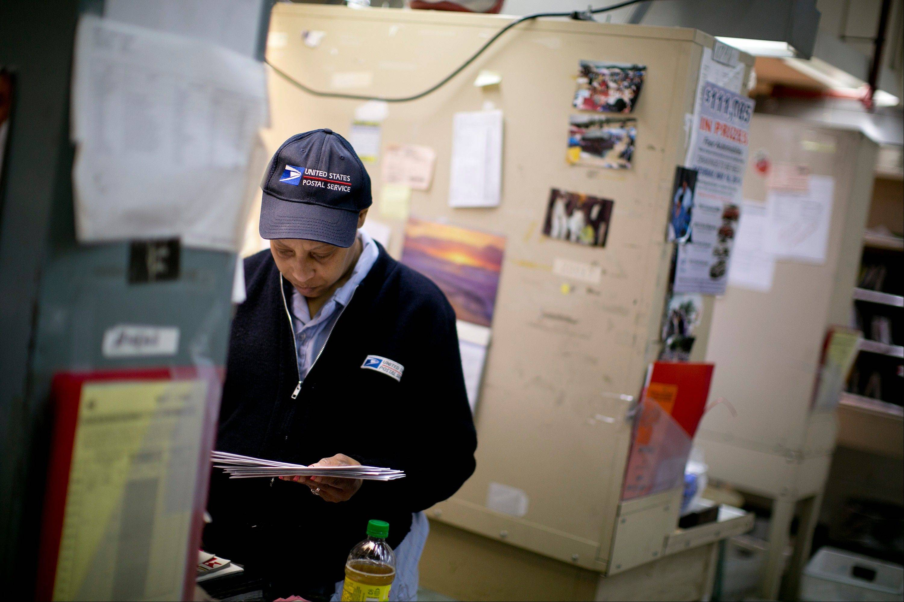 U.S. Postal Service (USPS) letter carrier Anja Wilson prepares mail for delivery Thursday at the Brookland Post Office in Washington, D.C.. The USPS is projecting a loss of as much as a $6 billion for the year.