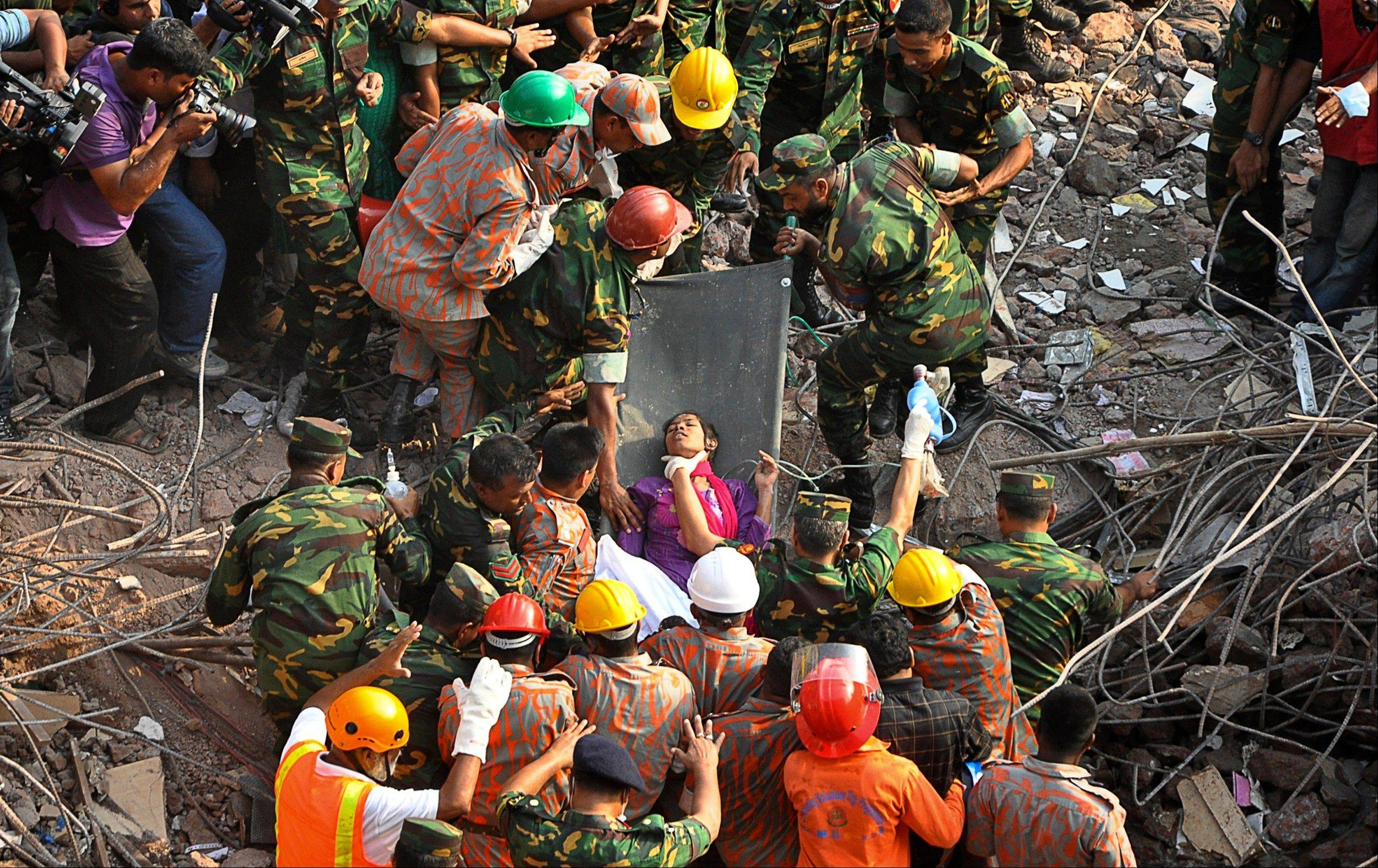 Rescuers carry a survivor pulled out from the rubble Friday of a building that collapsed in Saver, near Dhaka, Bangladesh. Rescue workers in Bangladesh freed the woman buried for 17 days inside the wreckage of a garment factory building that collapsed, killing more than 1,000 people. Soldiers at the site said her name was Reshma and described her as being in remarkably good shape despite her ordeal.