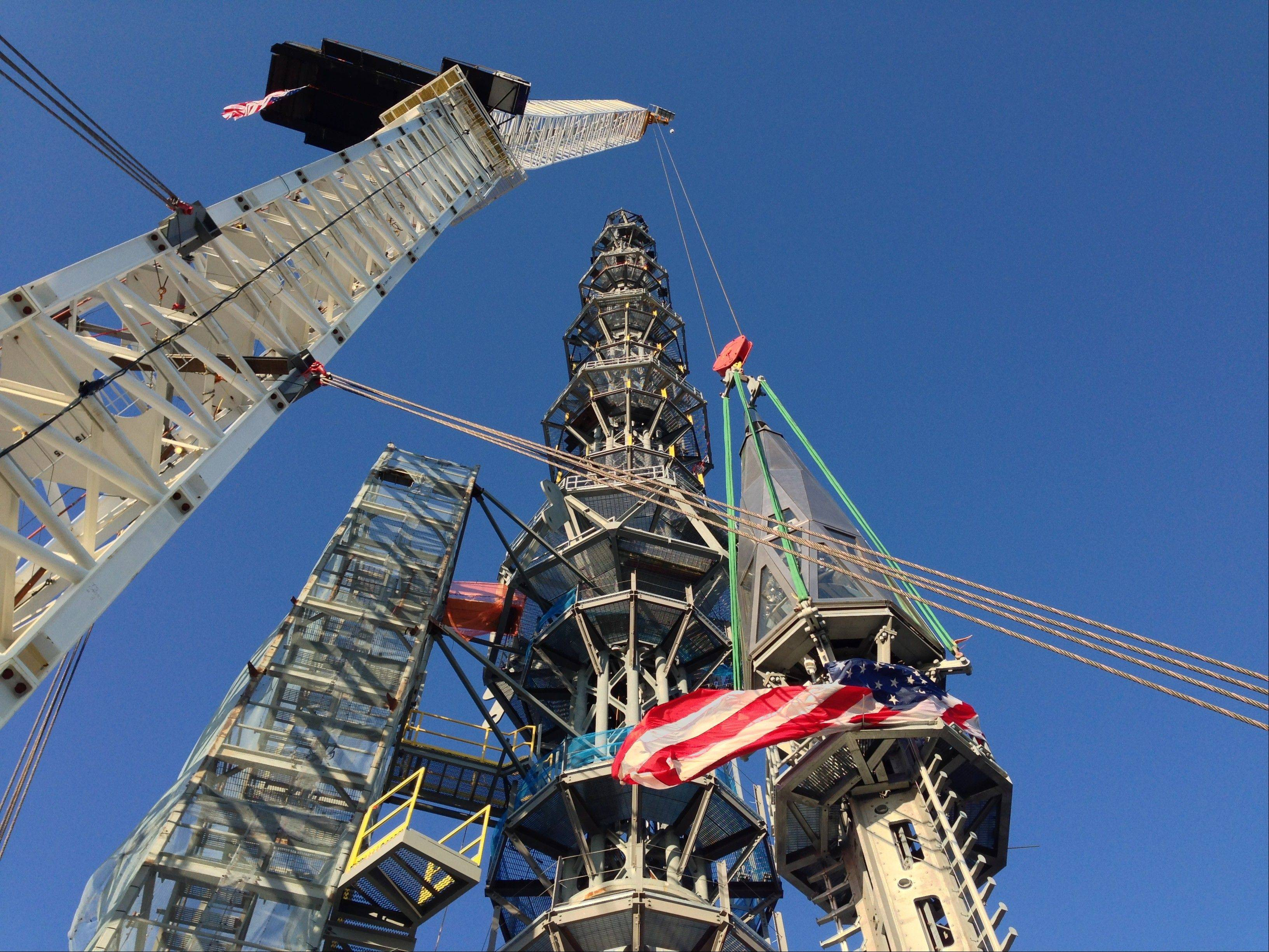 The silver spire topping One World Trade Center is fully installed on the building's roof, bringing the structure to its full, symbolic height of 1,776 feet Friday.