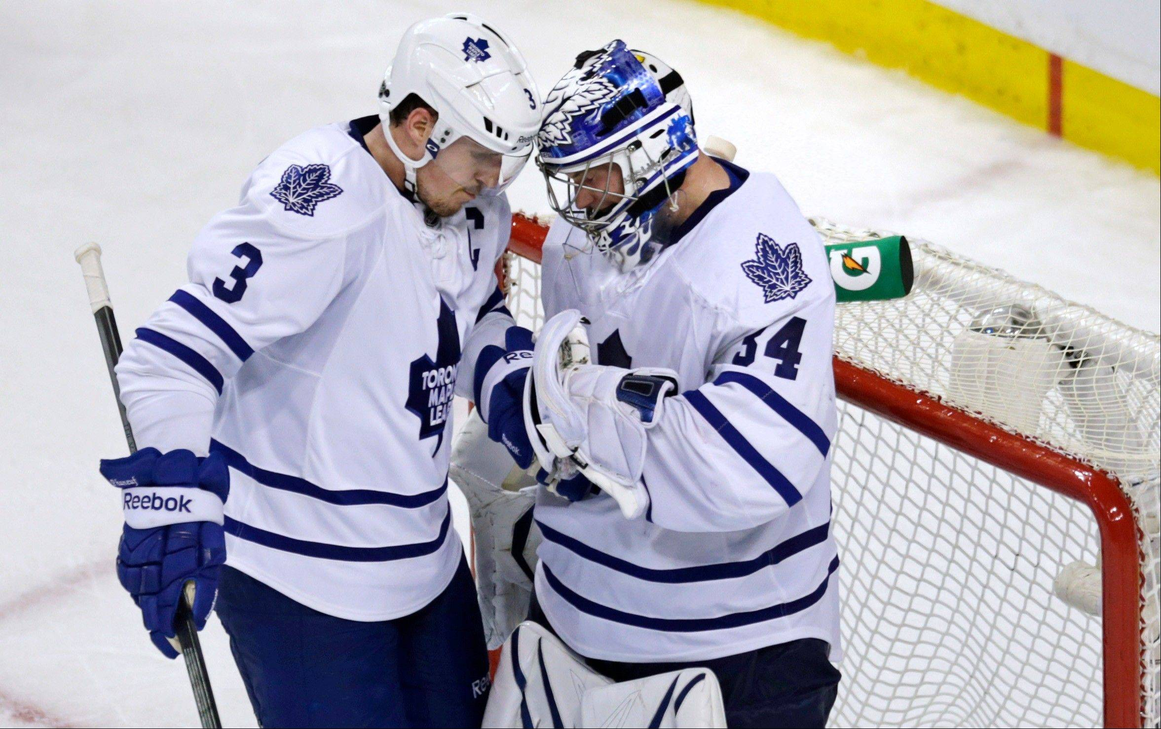 Toronto Maple Leafs goalie James Reimer, right, is congratulated by teammate Dion Phaneuf after the Maple Leafs defeated the Boston Bruins 2-1 in Game 5 of an NHL hockey Stanley Cup playoff series, in Boston on Friday, May 10, 2013. (AP Photo/Charles Krupa)