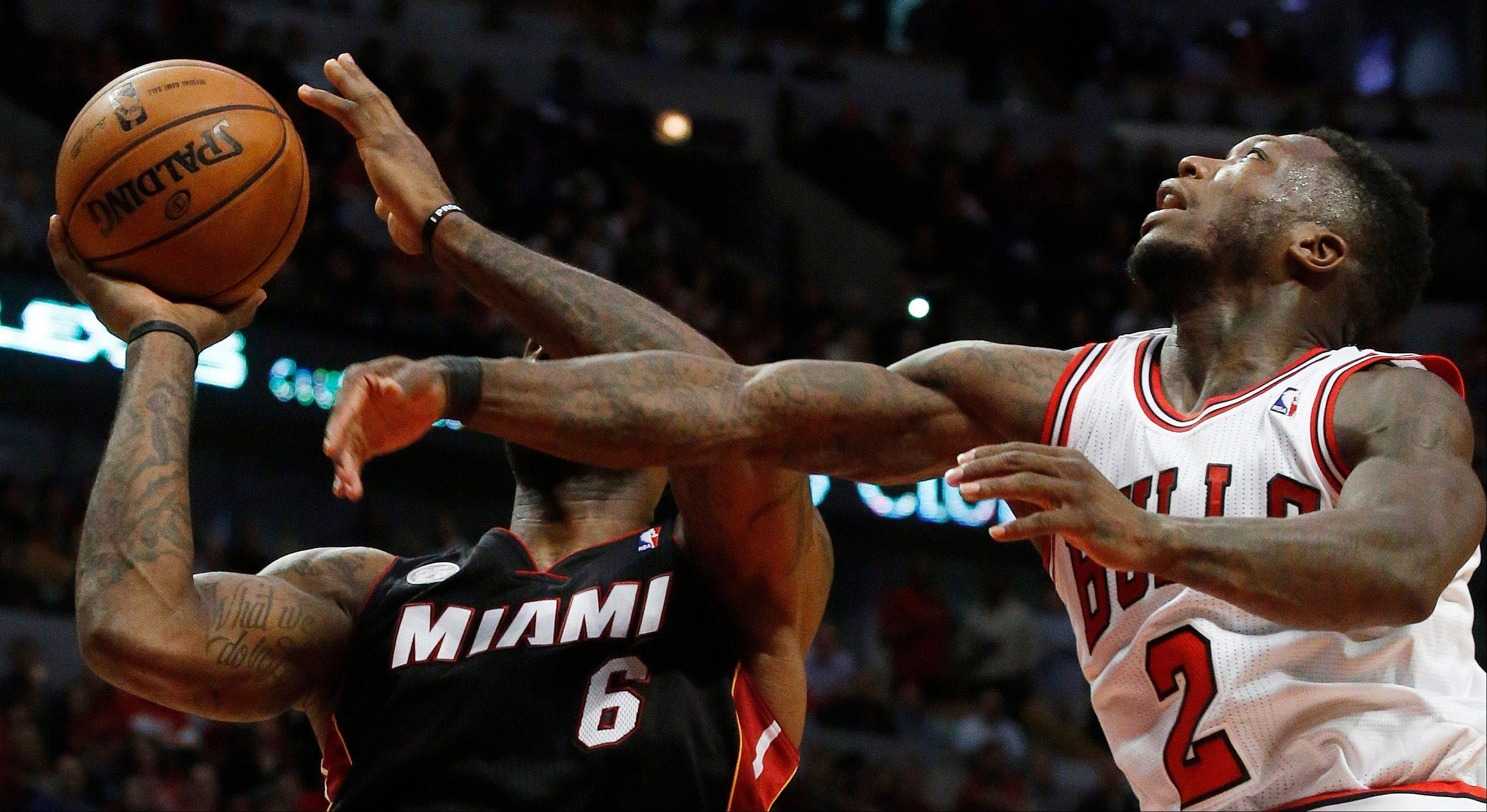 Miami Heat small forward LeBron James (6) heads to the hoop under the defense of Chicago Bulls point guard Nate Robinson (2) during the first half of Game 3 of an NBA basketball playoffs Eastern Conference semifinal on Friday, May 10, 2013, in Chicago. (AP Photo/Charles Rex Arbogast)