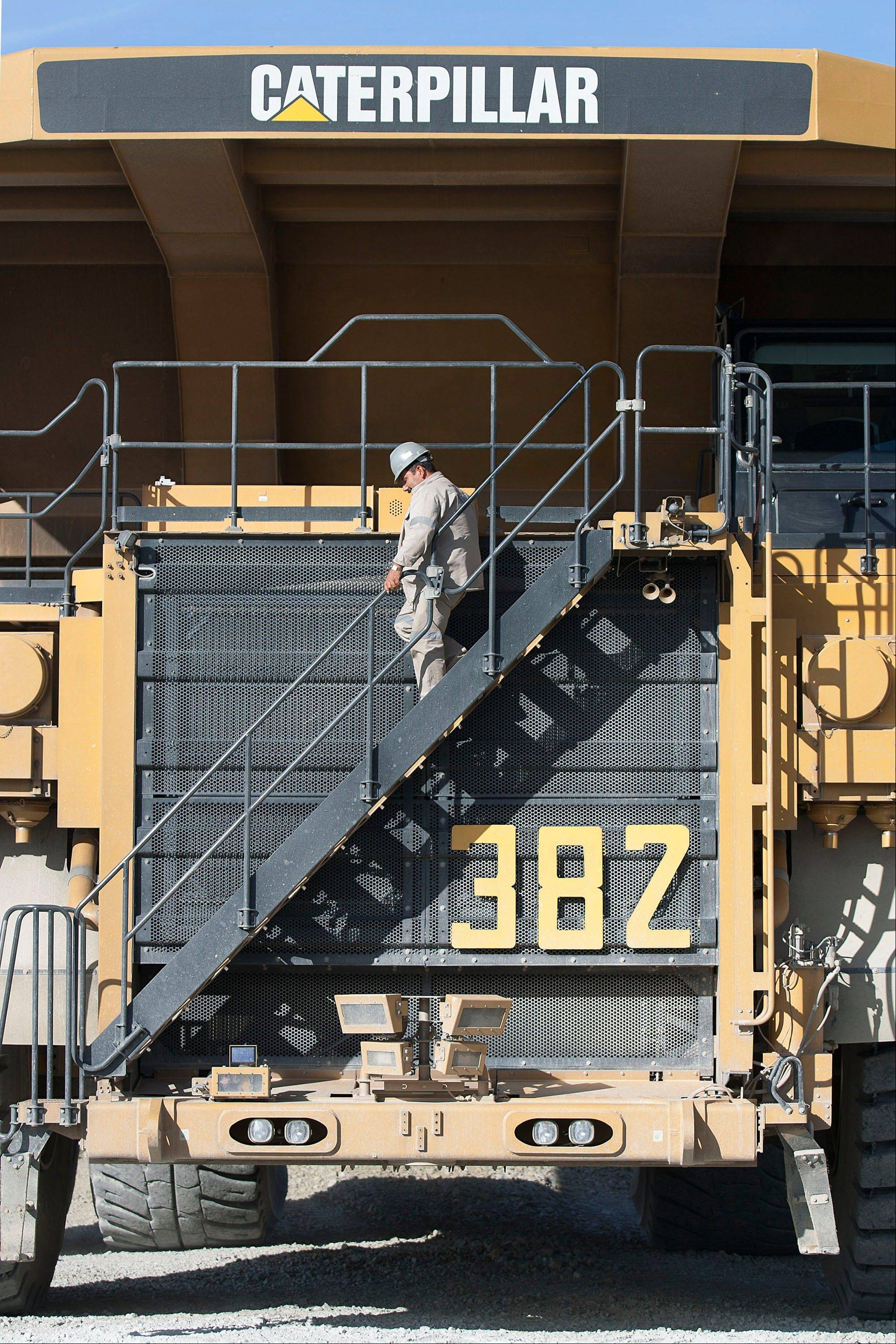 An worker descends the stairs or a Caterpillar Inc. truck Mnoday at Grupo Mexico SAB's La Caridad open pit copper mine in Sonora, Mexico. Exxon Mobil, Caterpillar and Alcoa -- Dow members whose fortunes are tied to the prices of crude oil and other basic materials -- closed down 1 percent or more on Friday.