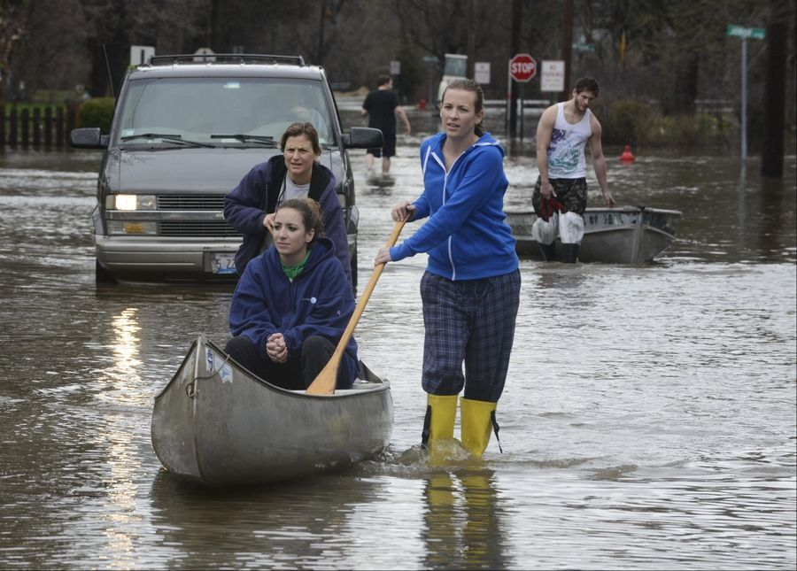 Rebecca Cavanaugh rides in a canoe pushed by her aunt, Tina Dace of Evanston, and her sister, Robin, as they leave the flooded Big Bend neighborhood in Des Plaines last month.
