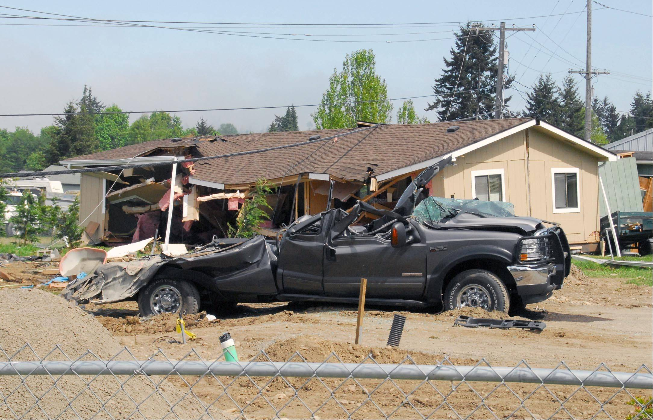 A crushed truck and a house knocked off its foundation sit as part of the aftermath of a rampage by a man driving a logging bulldozer on Friday in Port Angeles, Wash. At least three houses were destroyed and numerous smaller structures and vehicles were damaged in the rampage.