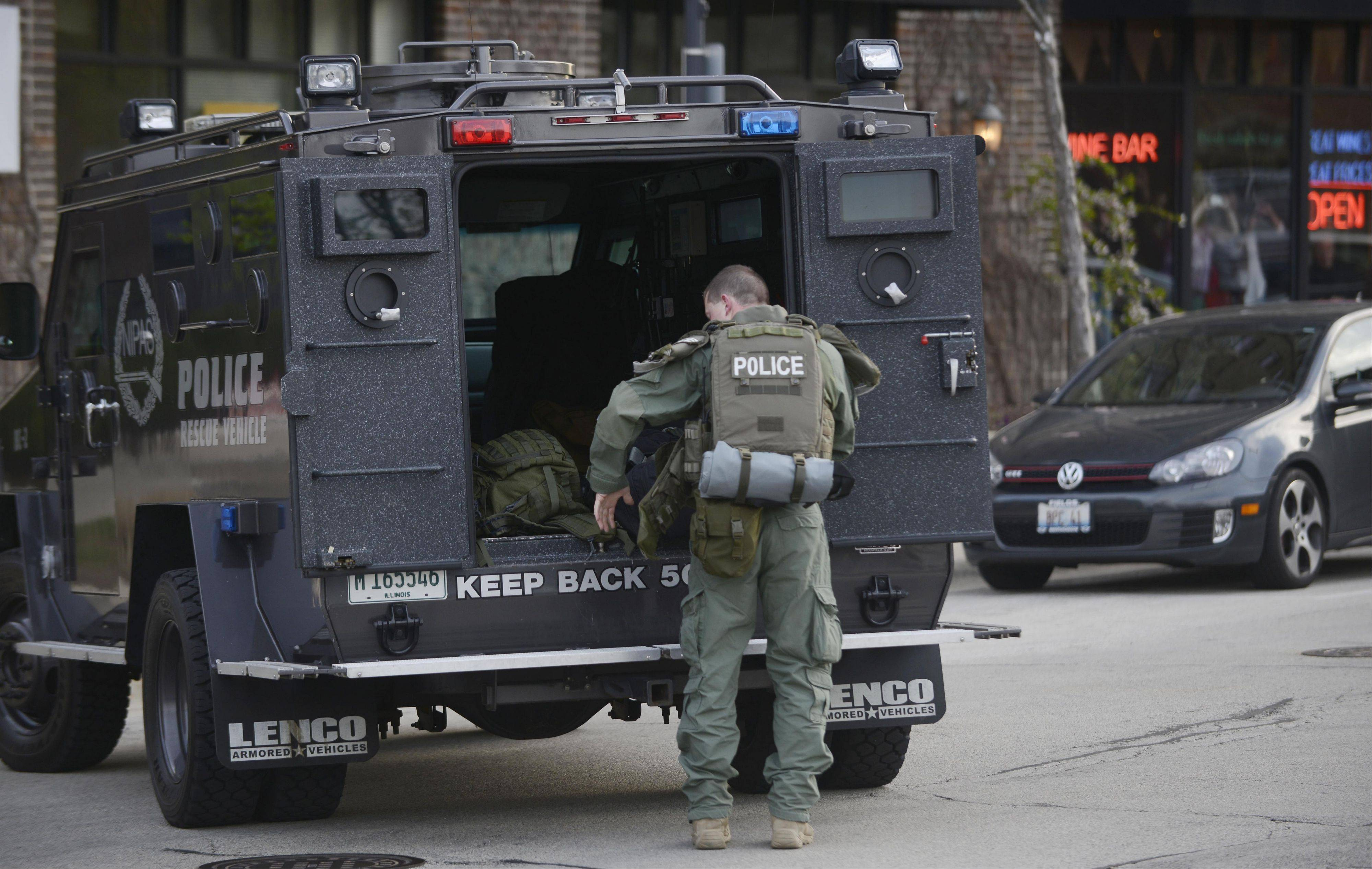 An officer equips himself at the back of an armored police vehicle during the May 4 police standoff in Arlington Heights.