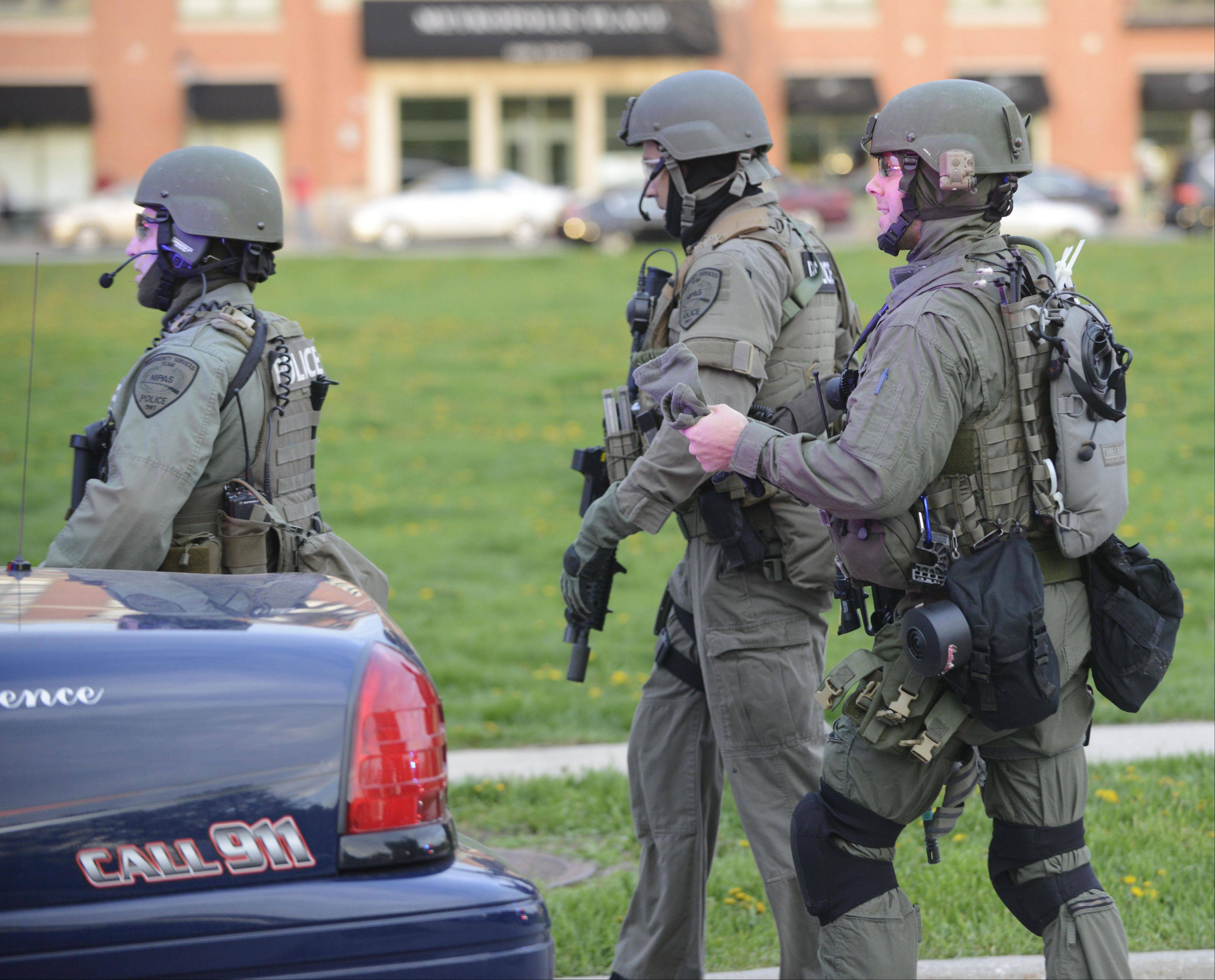 Heavily-armed officers walk toward the scene of Saturday evening's police standoff in Arlington Heights.