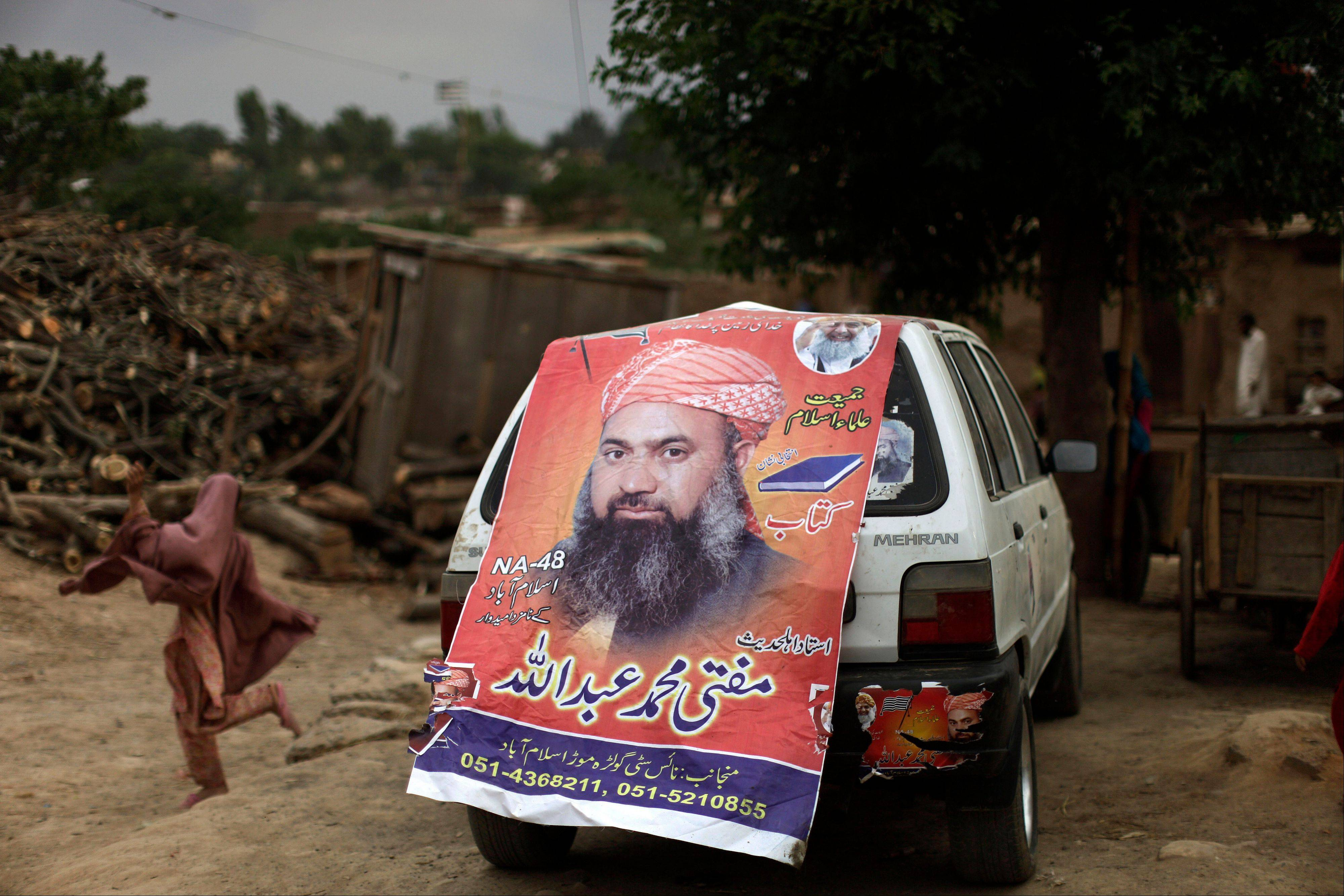 A Pakistani girl runs past a car Friday decorated with an election banner showing Mohammed Abdullah, a candidate of a pro-Taliban religious group Jamiat-e-Ulema Islam in a poor neighborhood on the outskirts of Islamabad, Pakis