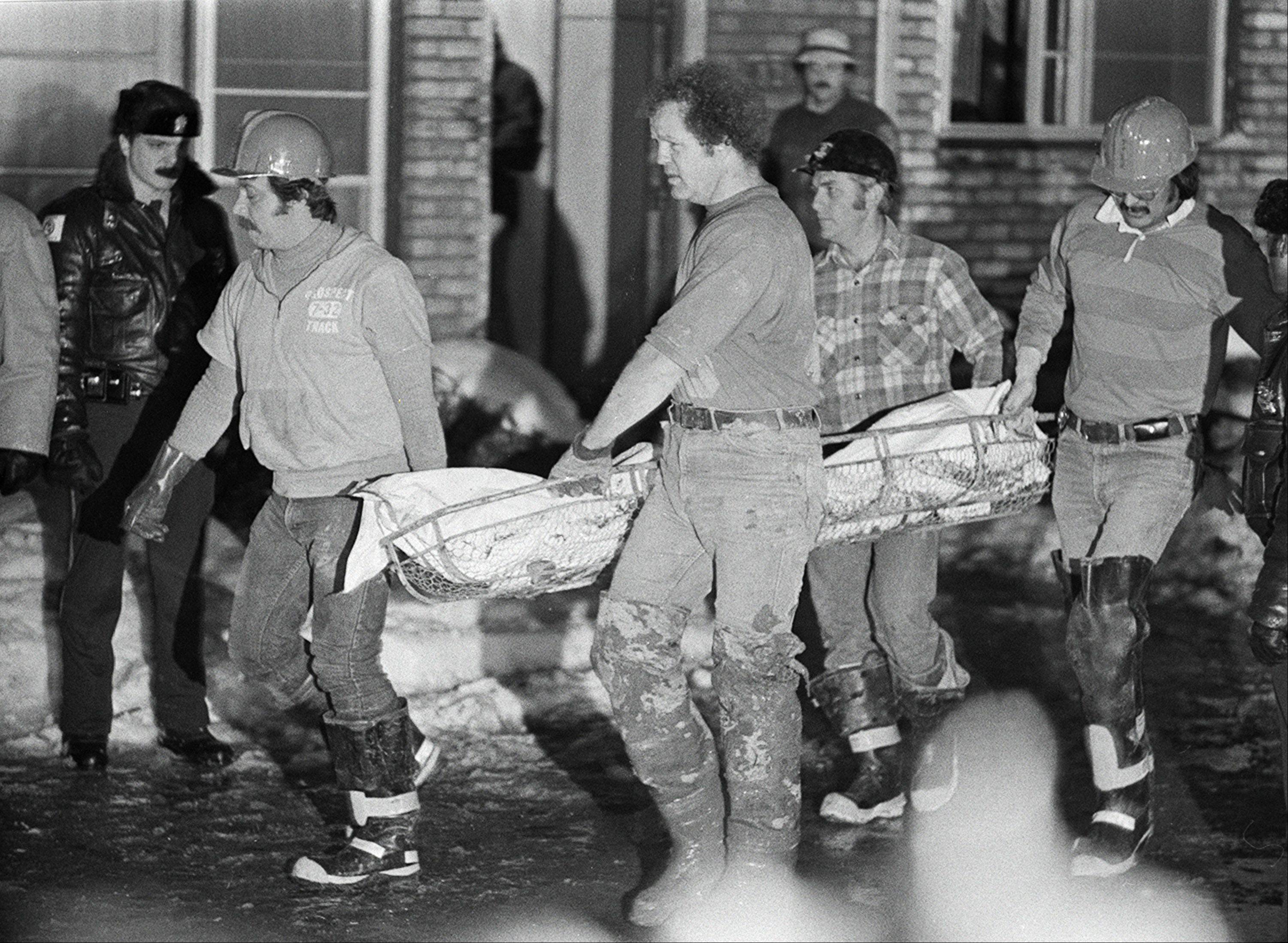 Police officers and firefighters remove one of the 28 bodies buried at the former Northwest suburban home of serial killer John Wayne Gacy in December 1978.