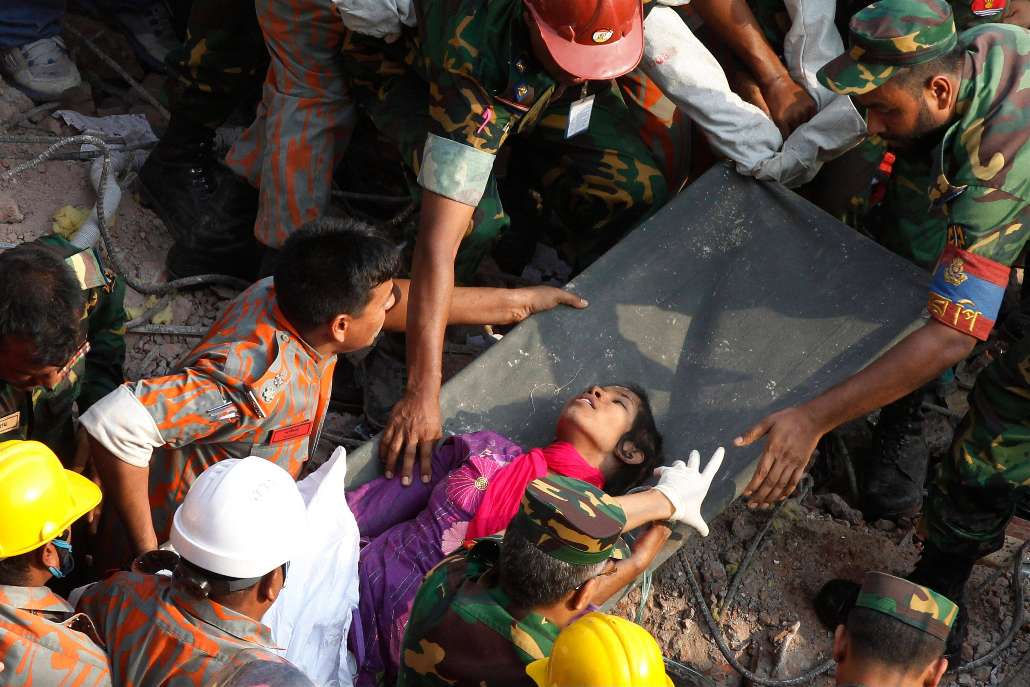 Survivor Reshma Begum lies on a stretcher after being pulled out from the rubble of a building that collapsed in Savar, near Dhaka, Bangladesh, Friday, May 10, 2013. Begum was working in a factory on the second floor of Rana Plaza when the building began collapsing around her April 24. She raced down a stairwell into the basement, where she became trapped near a Muslim prayer room in a wide pocket that allowed her to survive, she told the private Somoy TV.