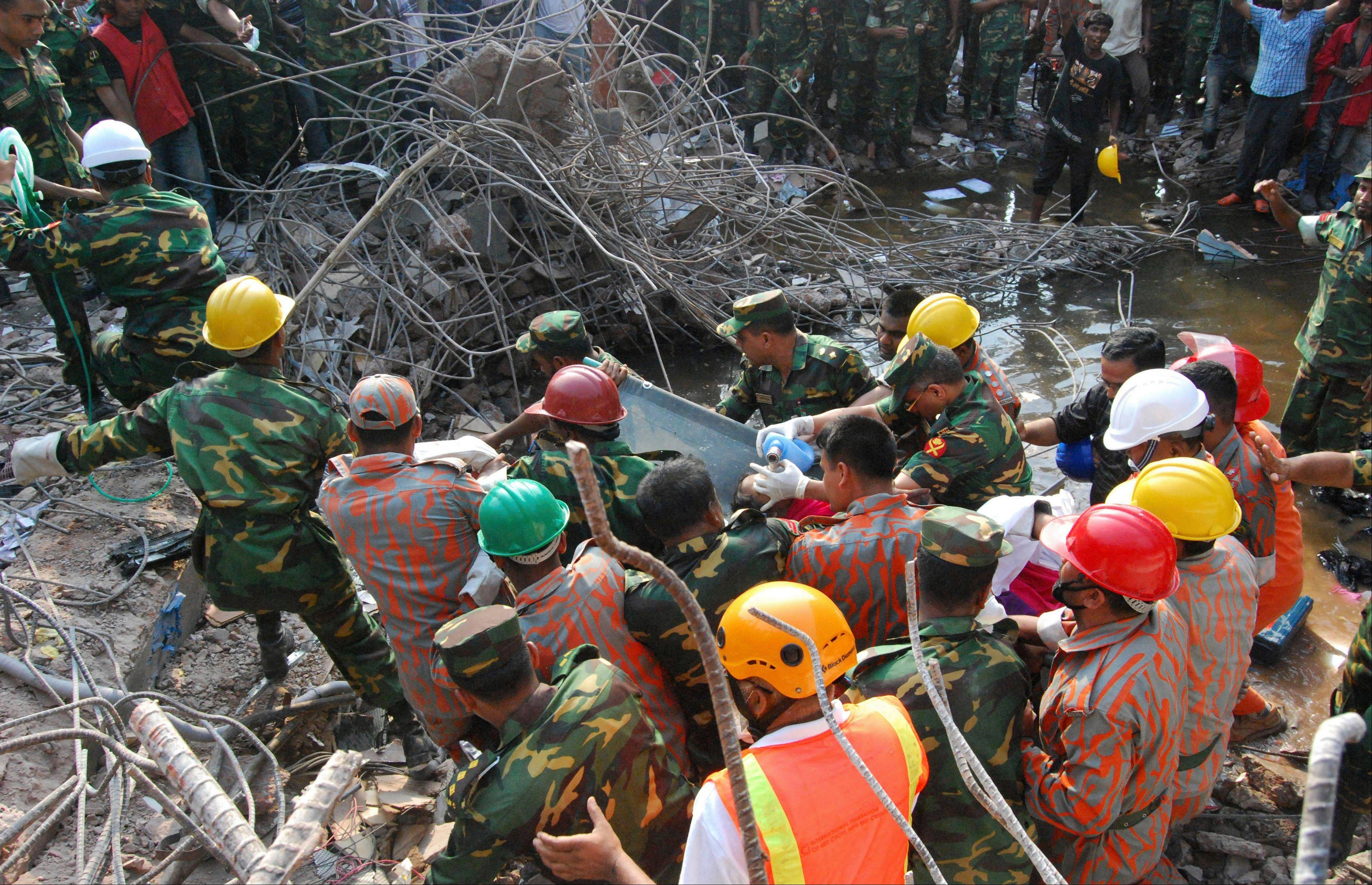 Rescuers carry a survivor pulled out from the rubble of a building that collapsed in Saver, near Dhaka, Bangladesh, Friday, May 10, 2013. Rescue workers in Bangladesh freed the woman buried for 17 days inside the wreckage of a garment factory building that collapsed, killing more than 1,000 people. Soldiers at the site said her name was Reshma and described her as being in remarkably good shape despite her ordeal.