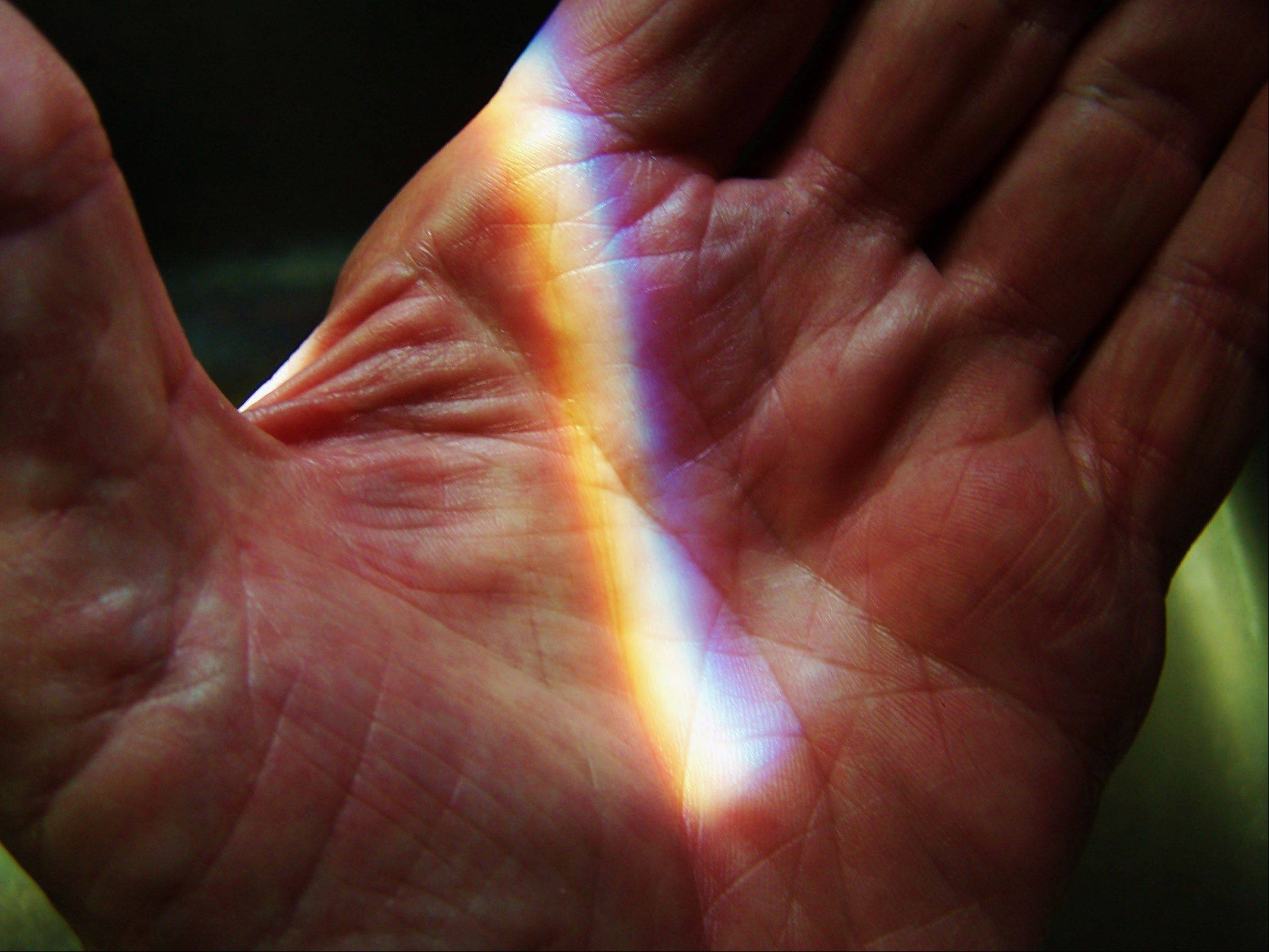 A small rainbow is formed in the light shining on Ken Kitzing's hand on Tuesday, April 30.