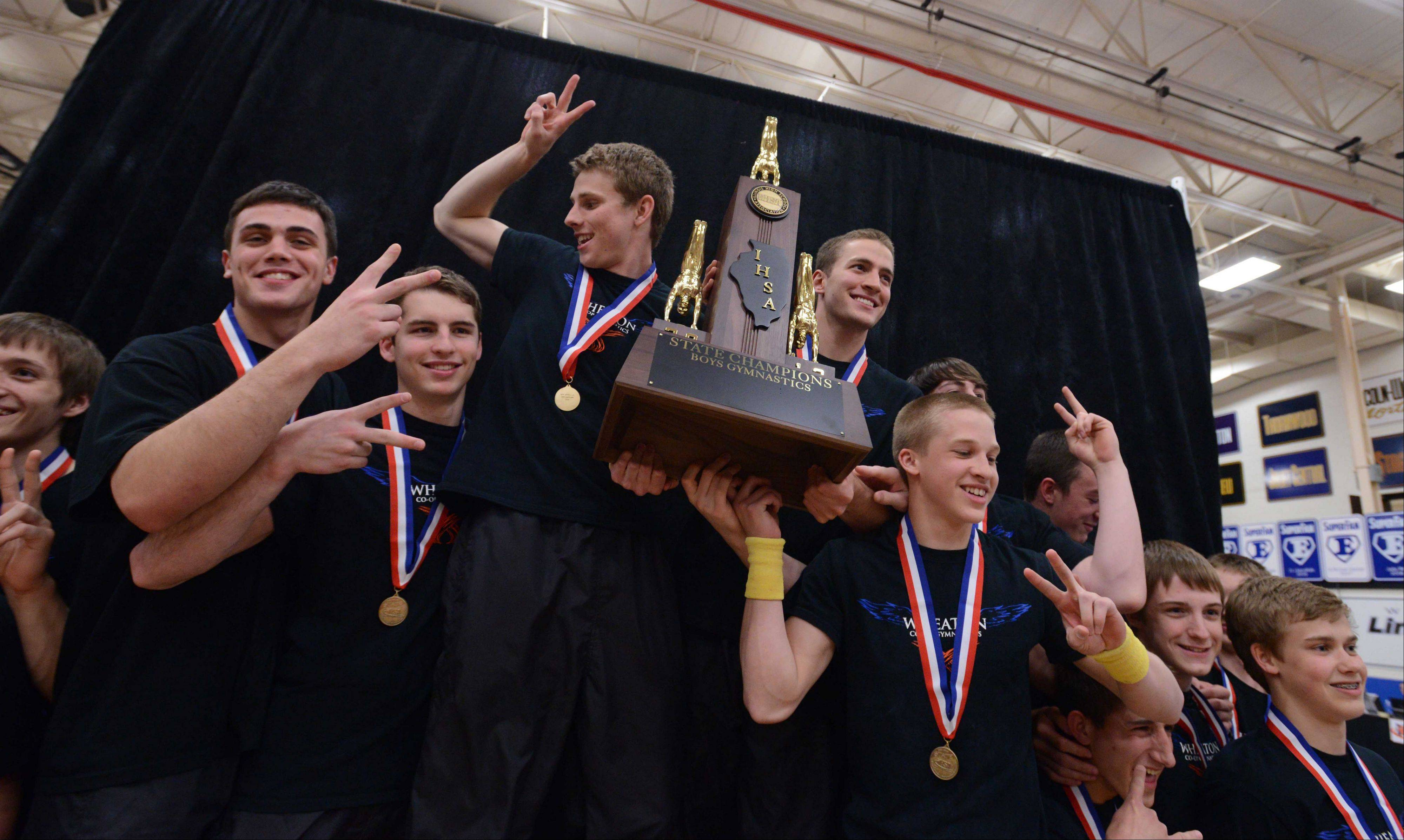 Wheaton co-op celebrates its repeat team championship in the boys gymnastics state finals Friday at Lincoln-Way East.