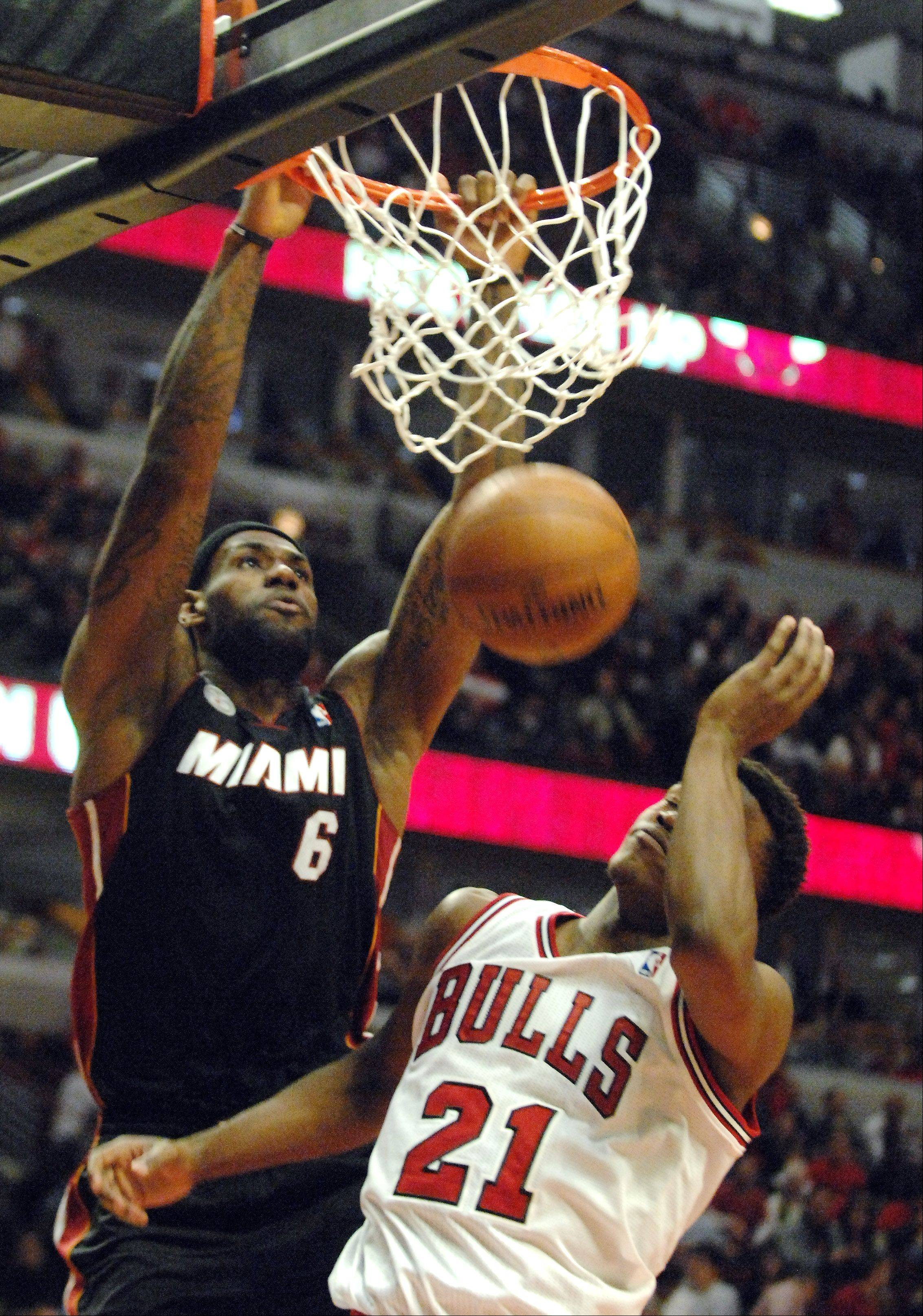 Miami Heat small forward LeBron James (6) dunks overChicago Bulls small forward Jimmy Butler (21) during game 3 of the NBA Eastern Conference semifinals at the United Center in Chicago Friday.