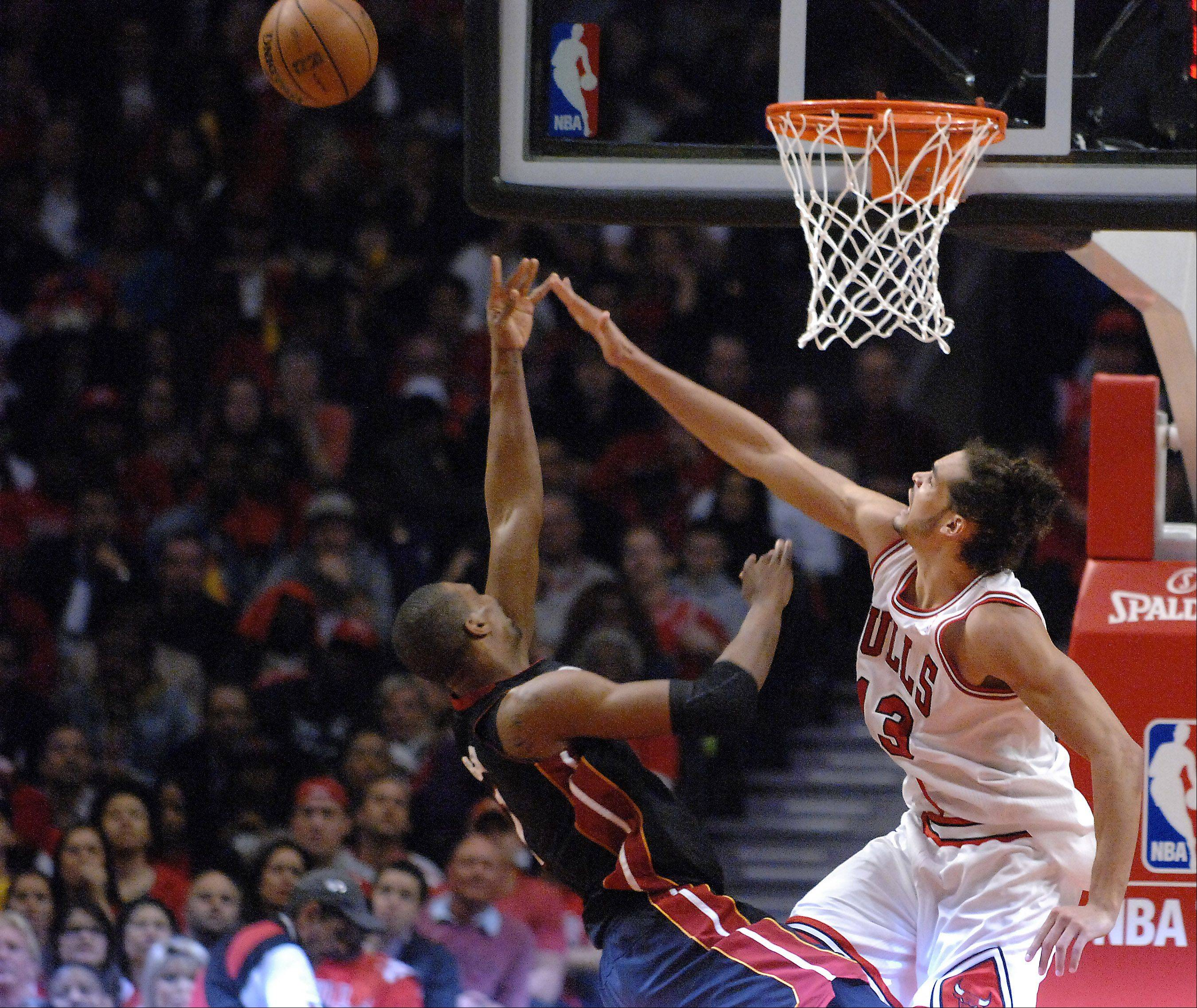 Chicago Bulls center Joakim Noah (13) blocks a shot by Miami Heat center Chris Bosh (1) during game 3 of the NBA Eastern Conference semifinals at the United Center in Chicago Friday.